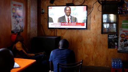 Men watch a television set as opposition leader Raila Odinga addresses the nation during a press conference, at the Mathare slum, in Nairobi, Kenya August 16, 2017.