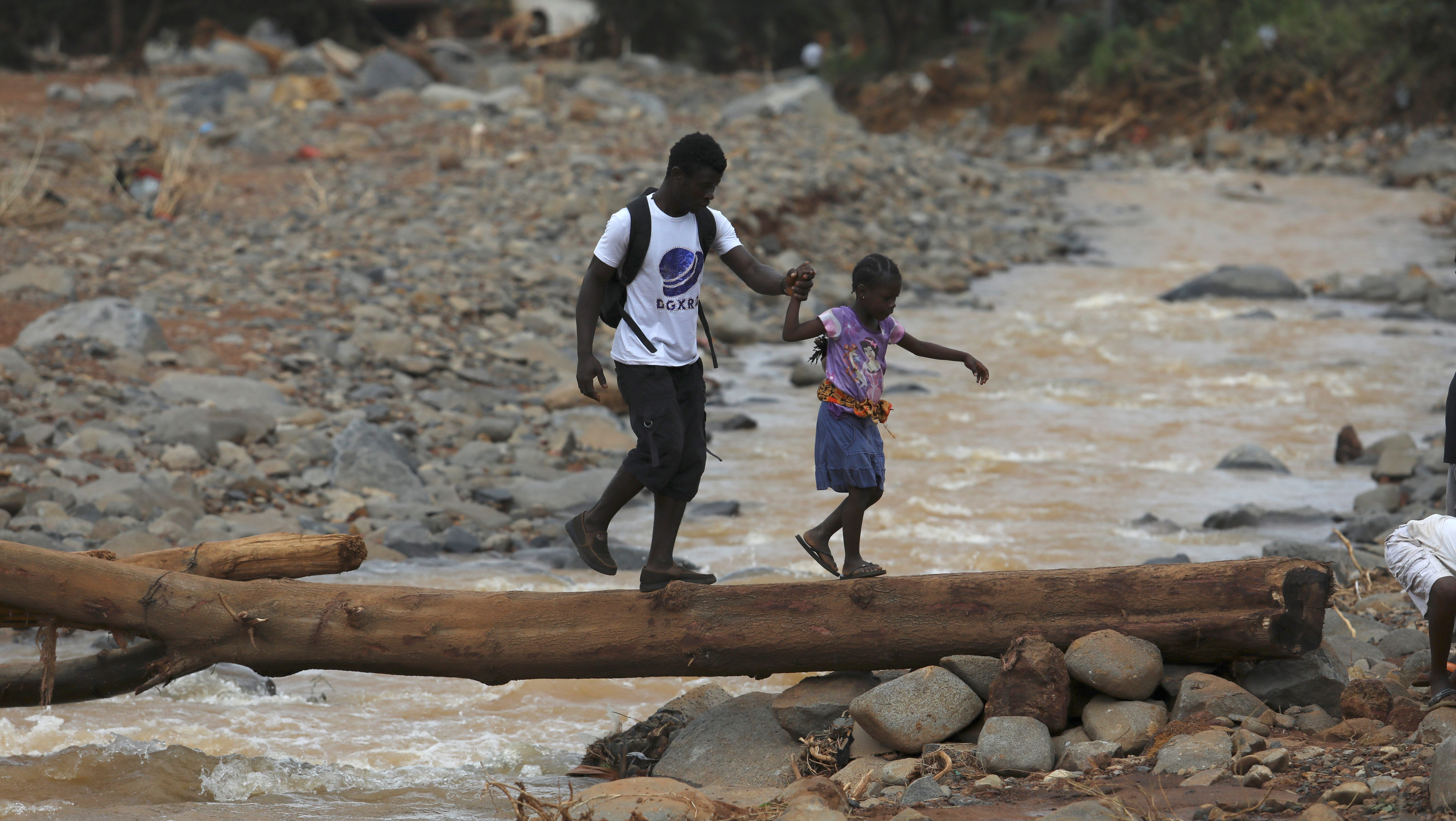 A man helps a girl cross a log bridge after the flash flood washed away the concrete bridge at Pentagon, in Freetown, Sierra Leone August 18, 2017.
