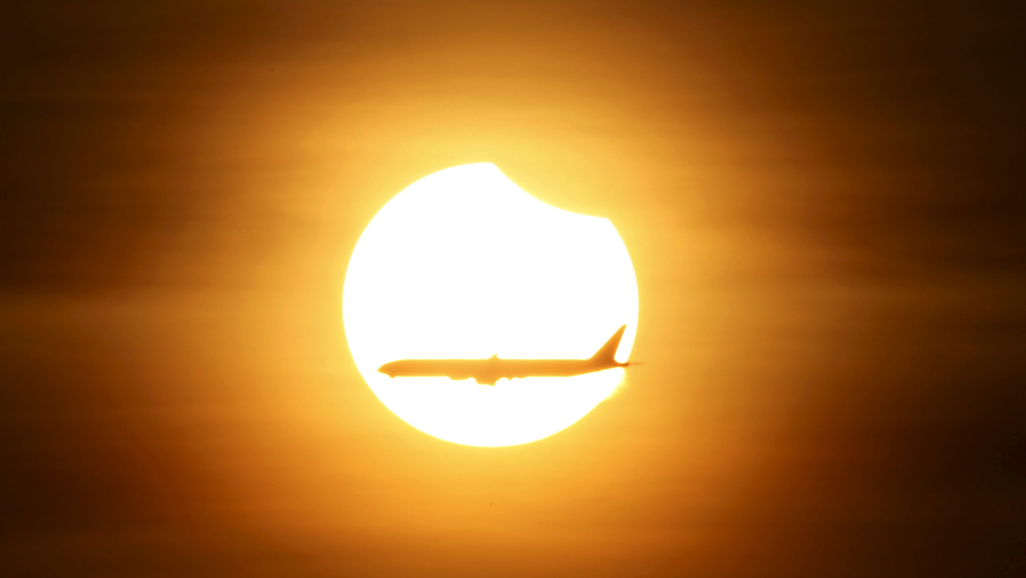 An aeroplane flies past the sun as it goes into a partial solar eclipse in Singapore March 9, 2016.