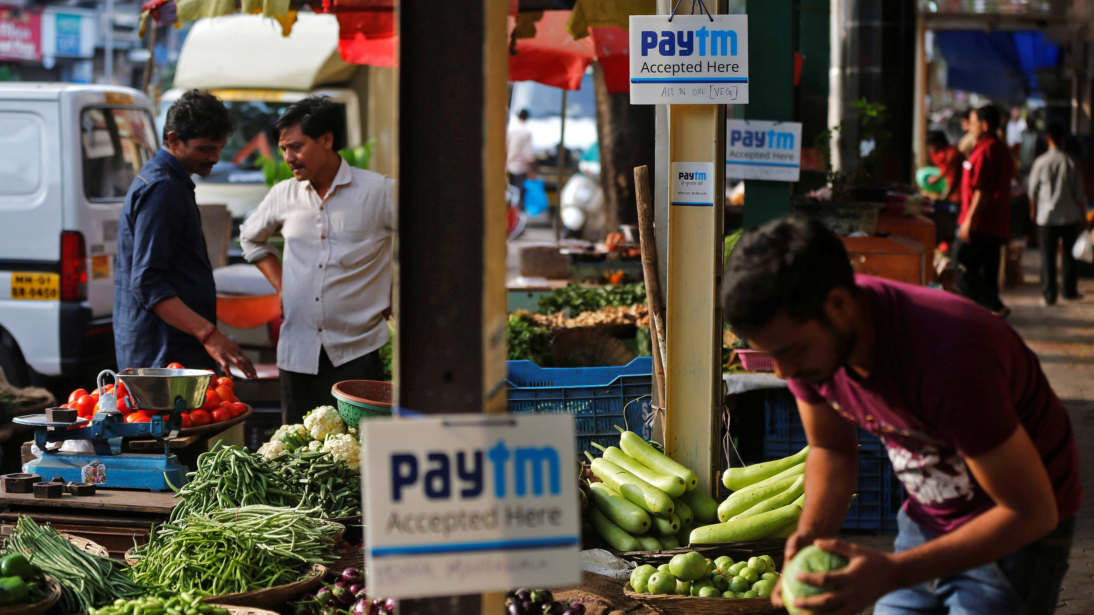 Advertisement boards of Paytm, a digital wallet company, are seen placed at stalls of roadside vegetable vendors as they wait for customers in Mumbai