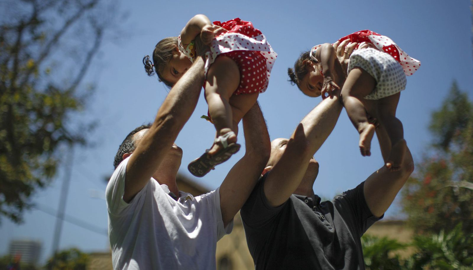 Jason Howe, 48, and Adrian Perez (L), 48, who were married in Spain, and again in California, hold their one-year-old twin daughters Clara (R) and Olivia at a playground in West Hollywood, California.