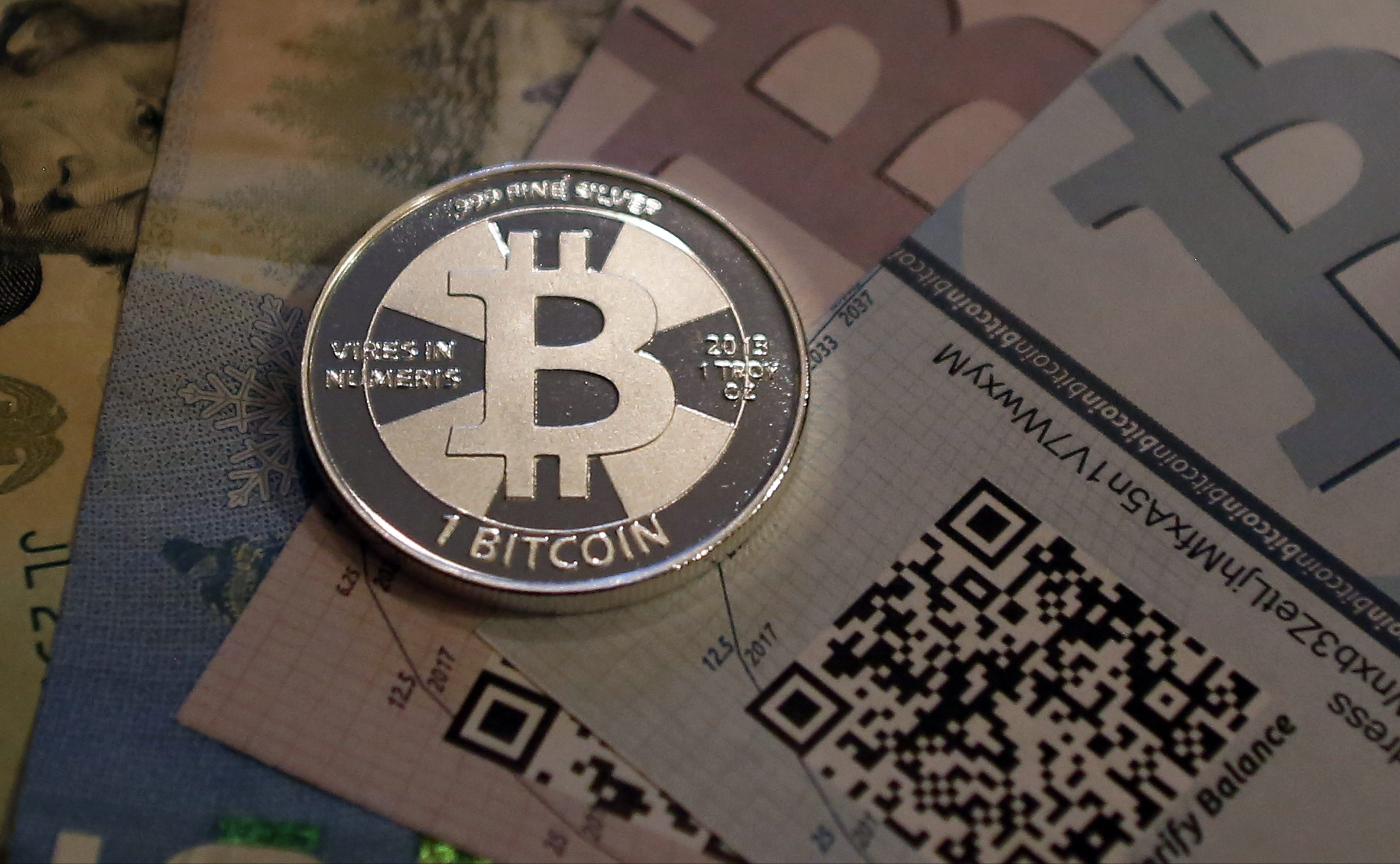 One of Bitcoin enthusiast Mike Caldwell's coins in this photo illustration at his office in Sandy, Utah, September 17, 2013. Bitcoins, touted by some experts as the future of money, gained in prominence during Europe's financial crisis as more people questioned the safety of holding their cash in the bank. Cameron and Tyler Winklevoss, currently making headlines with plans to launch a Bitcoin fund, said on Tuesday that they could see the digital currency becoming a country's official money.