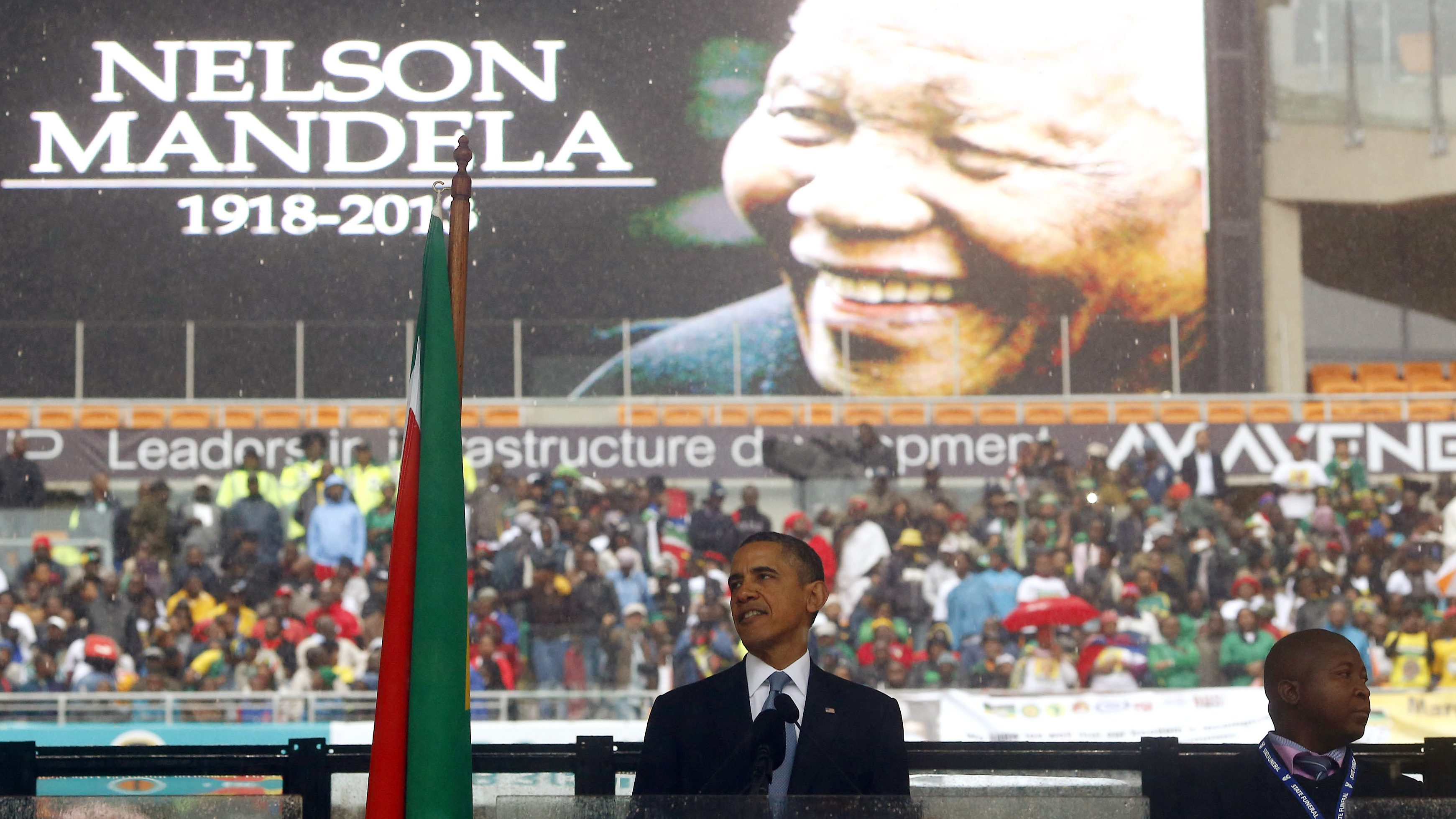 U.S. President Barack Obama gives a speech as a man passing himself off as a sign language interpreter (R) folds his hands during a memorial service for late South African President Nelson Mandela at the FNB soccer stadium in Johannesburg December 10, 2013.
