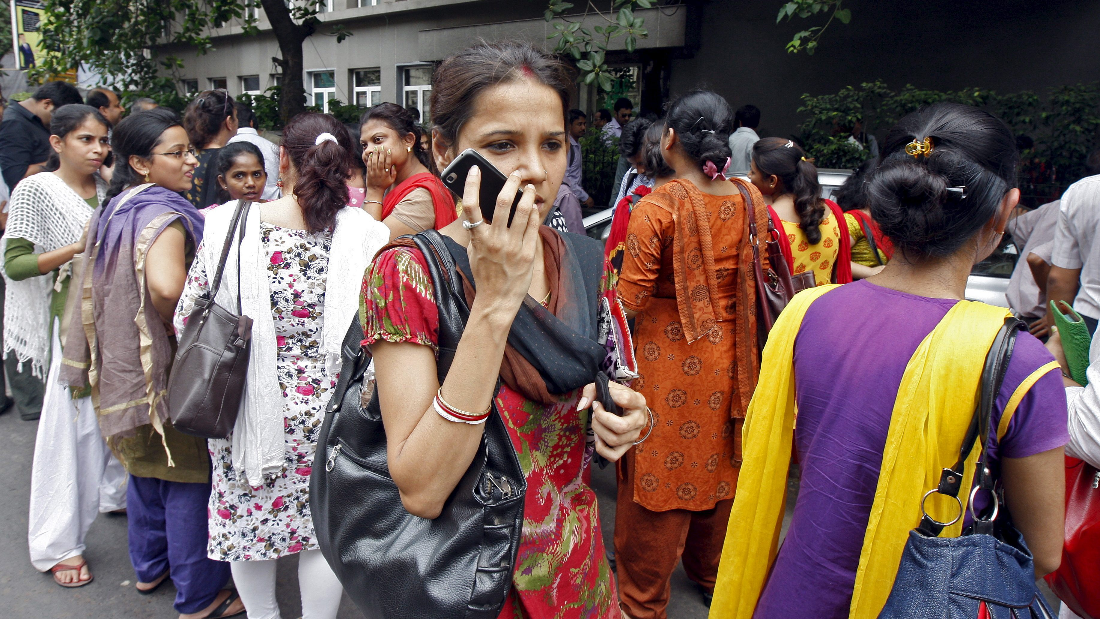 A woman speaks on her mobile phone as she stands with others after vacating their office buildings following an earthquake in Kolkata, India, May 12, 2015. At least four people were killed in a central Nepal town on Tuesday after a 7.3 earthquake shook the Himalayan nation, just weeks after a devastating temblor killed more than 8,000 people and damaged hundreds of thousands of buildings. The U.S. Geological Survey said Tuesday's earthquake was centred 68 km (about 42 miles) west of the town of Namche Bazar, close to Mount Everest and the border with Tibet. A magnitude 7.3 quake, it was felt as far apart as New Delhi and Dhaka, the capital of Bangladesh. REUTERS/Rupak De Chowdhuri  - RTX1CK76