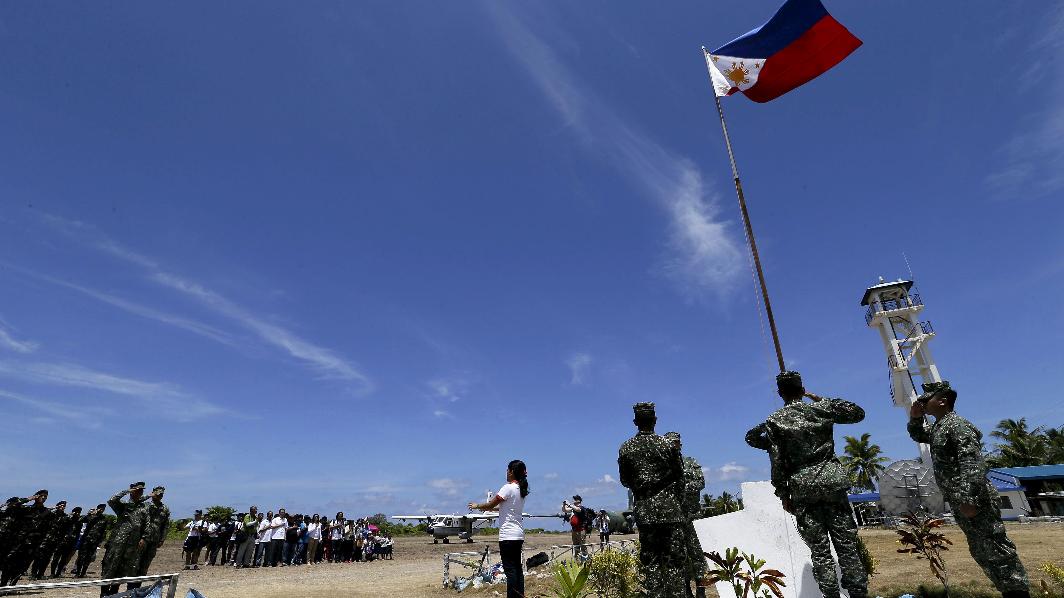 Filipino residents and soldiers conduct a flag raising ceremony during the visit of Armed Forces of the Philippines military chief General Gregorio Catapang in Thitu Island at the Spratly group of islands in the South China Sea, May 11, 2015.