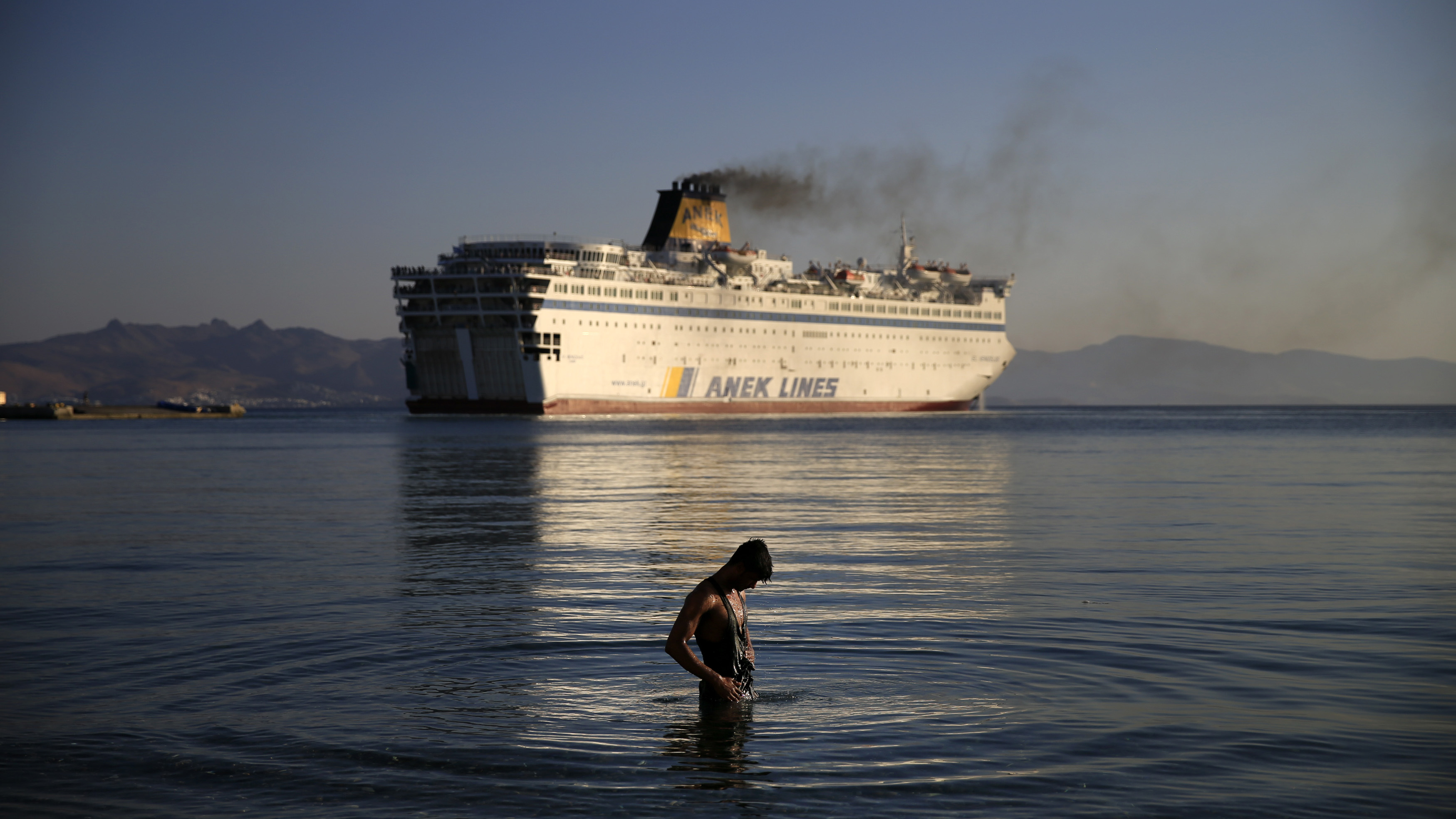 """A migrant washes as the passenger ship """"Eleftherios Venizelos"""" leaves the port on the Greek island of Kos, August 19, 2015. A passenger ship carrying Syrian refugees set sail from the Greek island of Kos on Wednesday, heading for the mainland as authorities struggle to cope with a wave of arrivals. The Greek coast guard's office said the ship, which has acted as a floating accommodation and registration centre since Sunday, was heading for the northern port of Thessaloniki, Greece's second biggest city.   REUTERS/Alkis Konstantinidis TPX IMAGES OF THE DAY - RTX1OQH3"""
