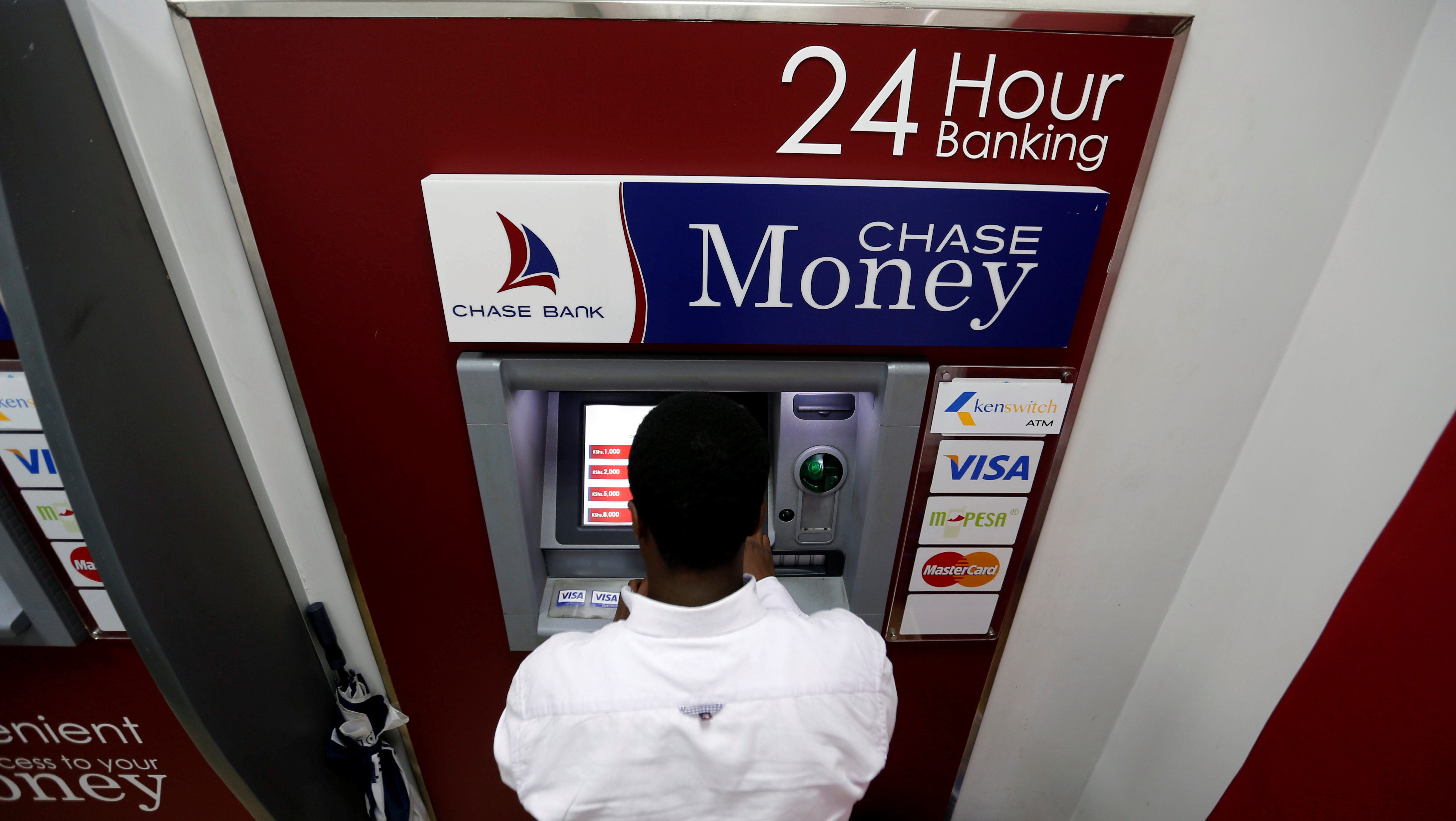 A man uses an ATM at a Chase Bank branch, now managed by Kenya Commercial Bank after its reopening in downtown Nairobi