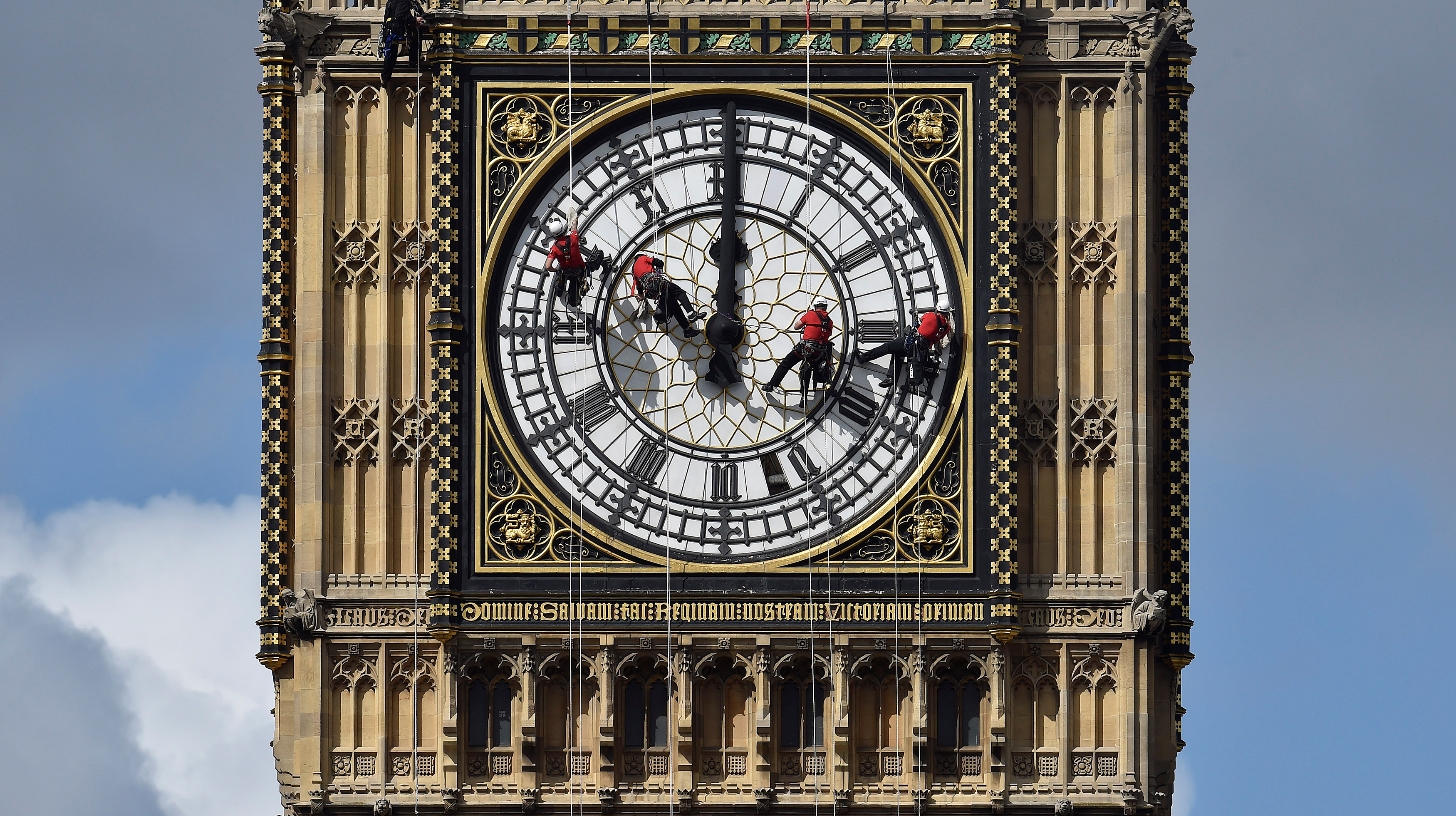 Cleaners abseil down one of the faces of Big Ben, to clean and polish the clock face, above the Houses of Parliament, in central London August 19, 2014.