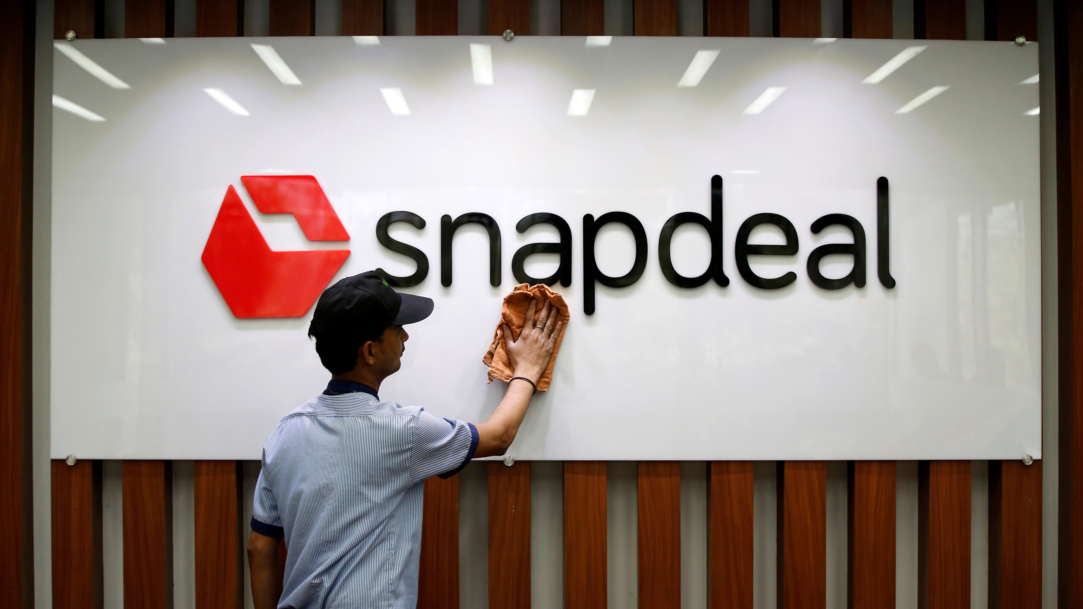 An employee cleans a Snapdeal logo at its headquarters in Gurugram on the outskirts of New Delhi, India, April 3, 2017.   Picture taken April 3. REUTERS/Adnan Abidi - RTX33YCE
