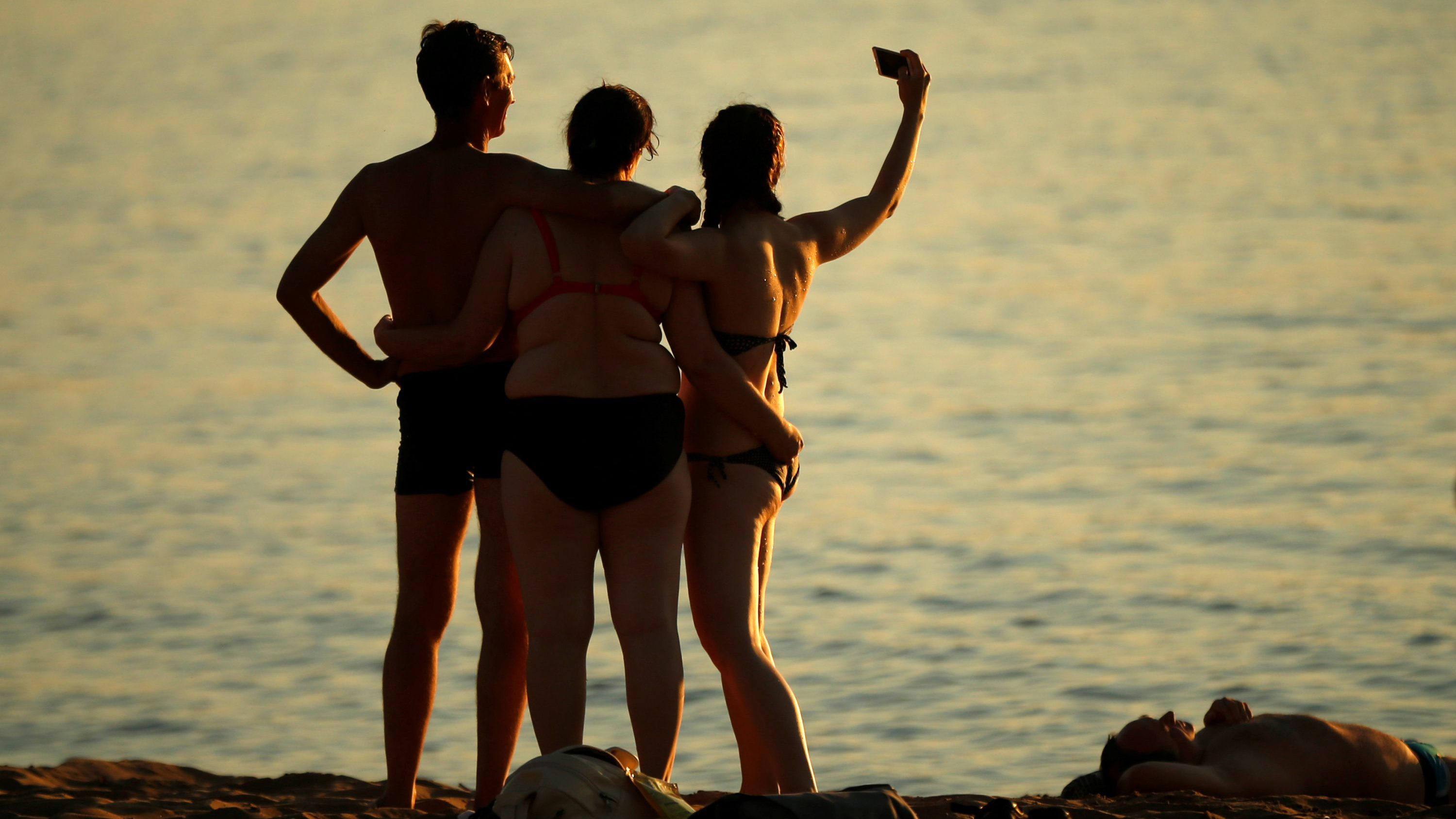 People take a selfie during sunset on the beach along the Volga river in Samara, Russia, July 18, 2017.