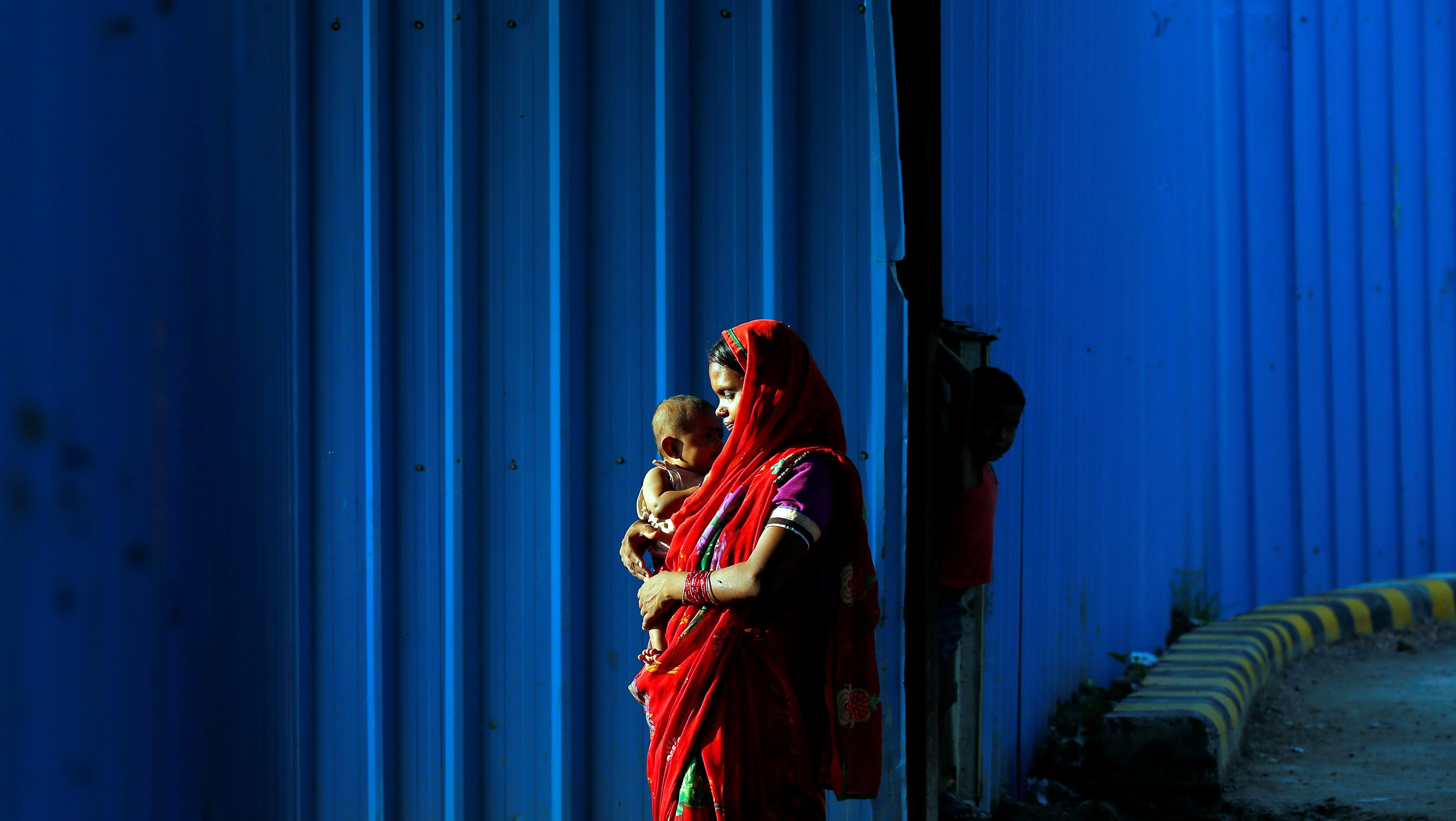 A woman day labourer holds her baby beside a construction site in New Delhi, India July 20, 2017. REUTERS/Cathal McNaughton - RTX3C83E