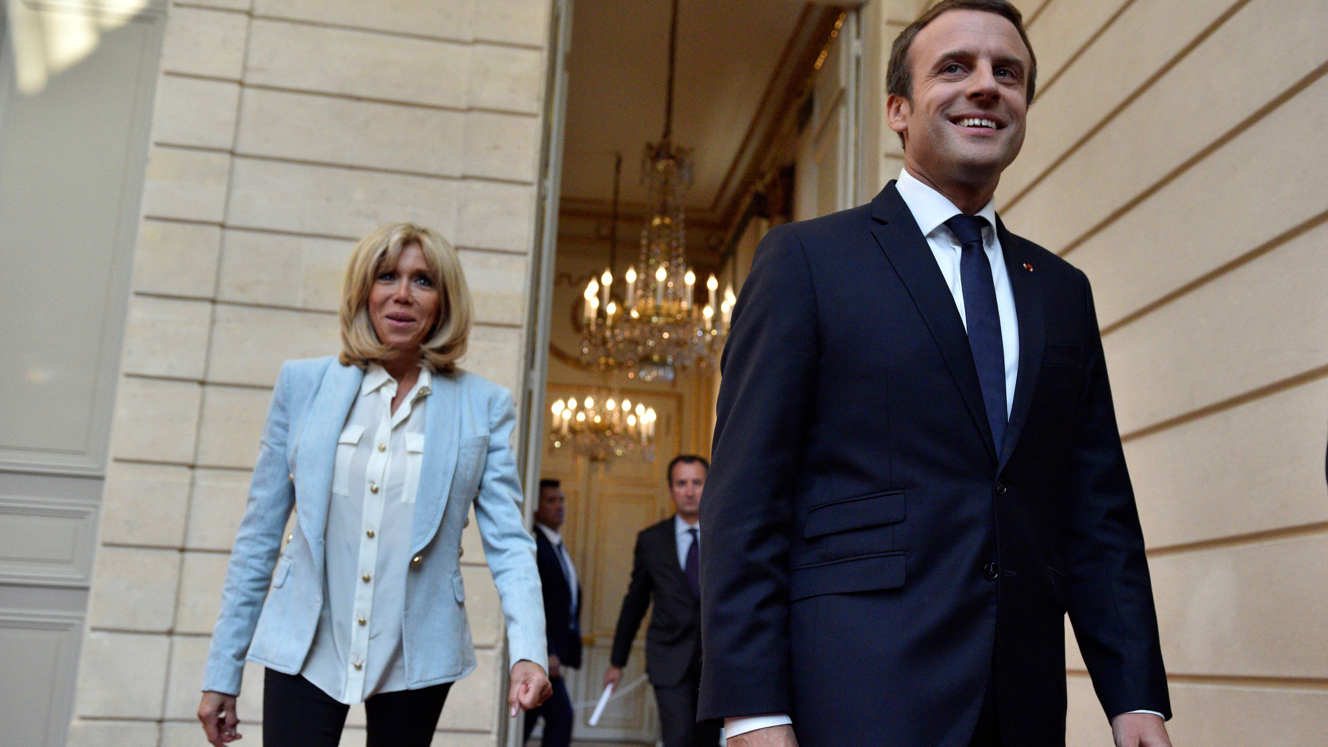 French President Emmanuel Macron and his wife Brigitte Macron arrive to attend a concert given by the Pierre Claver Association at the Elysee Palace in Paris