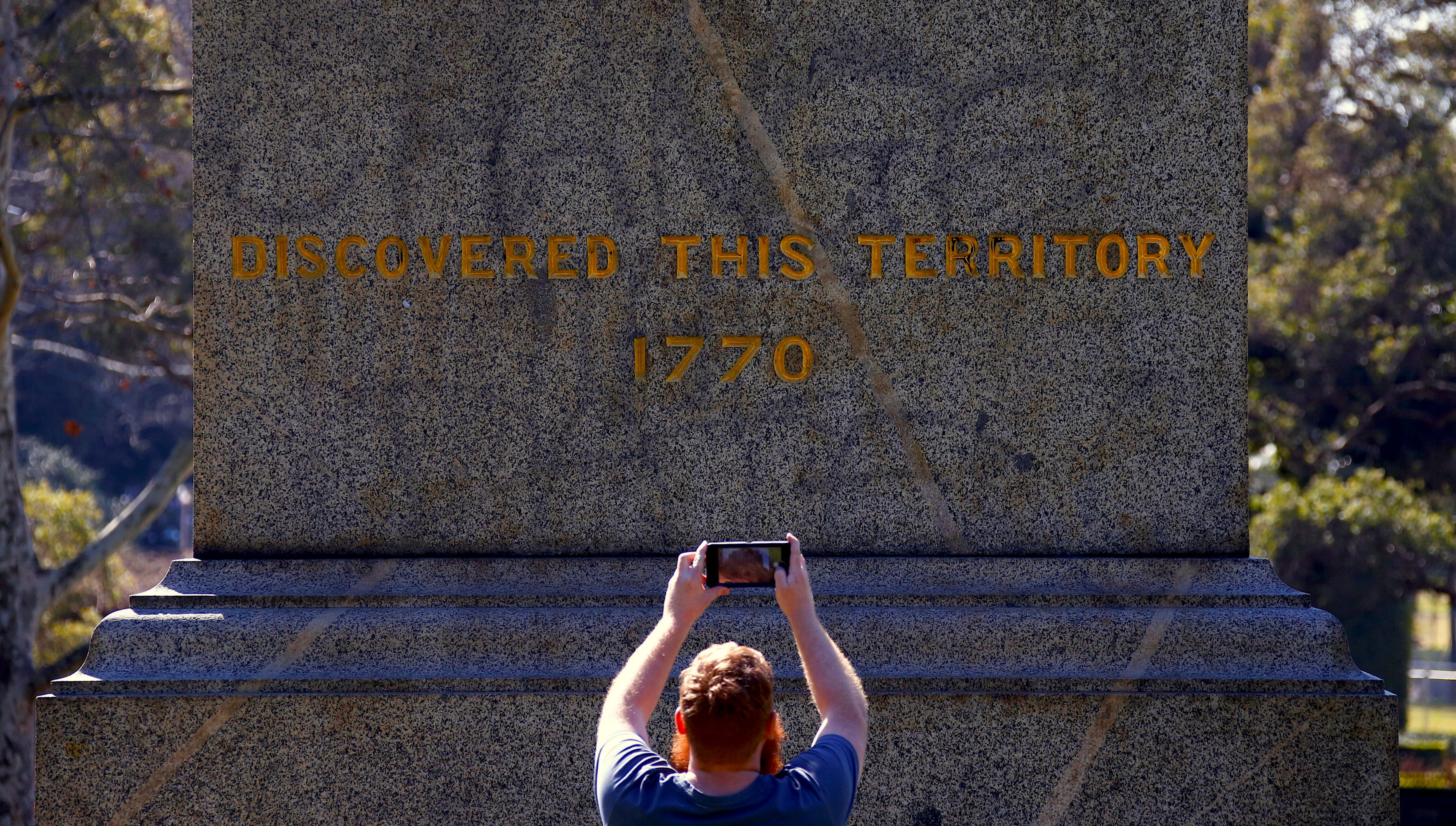 A member of the public uses his phone to take a photograph of the slogan 'Change the Date' that was sprayed over the inscription 'Discovered this Territory 1770' on a statue of British explorer Captain James Cook located in Hyde Park, in central Sydney