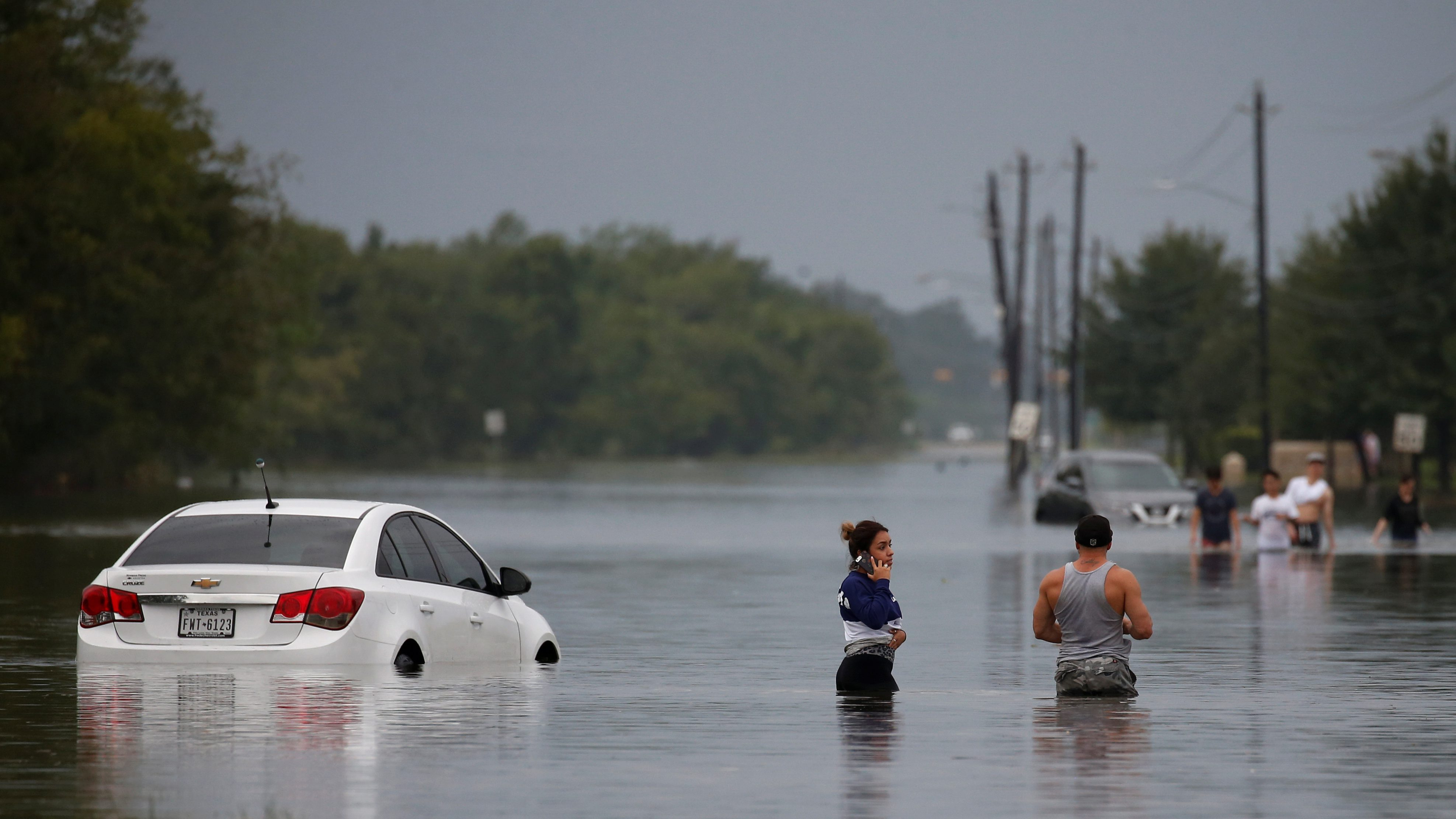 Residents wade through flood waters from Tropical Storm Harvey in Houston, Texas, U.S. August 27, 2017.
