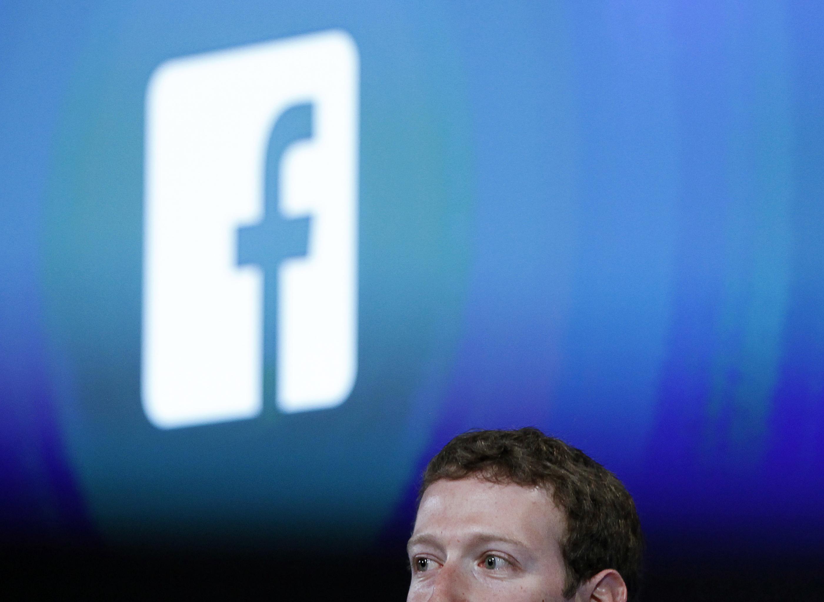 Mark Zuckerberg stands in front of the Facebook logo.