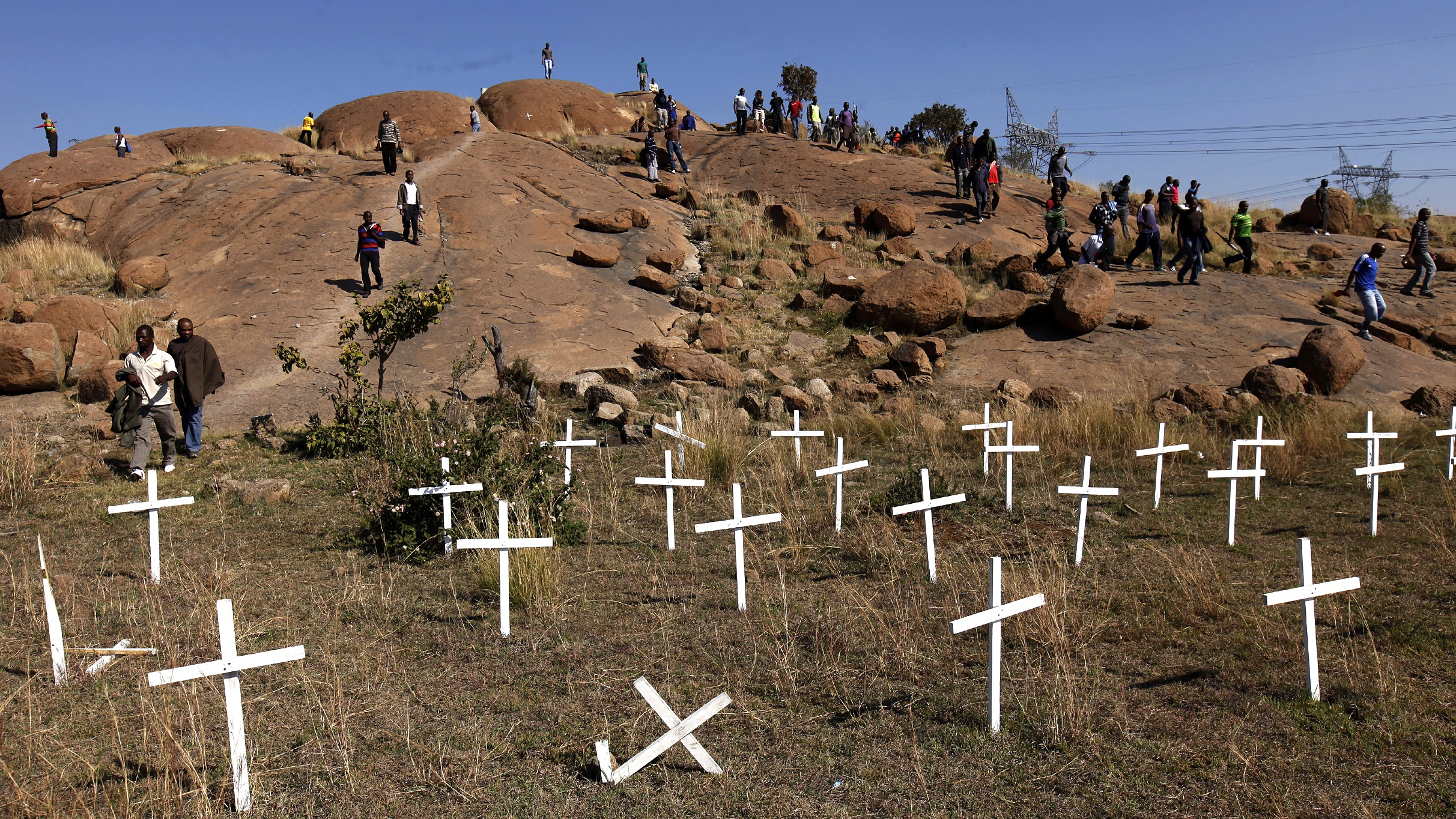 """Members of the mining community walk near crosses placed at a hill known as the """"Hill of Horror"""", where 43 miners died during clashes with police last year, during a strike at Lonmin's Marikana platinum mine in Rustenburg, 100 km (62 miles) northwest of Johannesburg, May 14, 2013. South African workers of world No. 3 platinum producer Lonmin launched a wildcat strike on Tuesday, halting all of the company's mine operations and reigniting fears of deadly unrest that rocked the industry last year. The platinum belt towns of Rustenburg and Marikana, which saw violent strikes at Lonmin and other platinum producers last year, are a flashpoint of labour strife with tensions running high over looming job cuts and wage talks. REUTERS/Siphiwe Sibeko (SOUTH AFRICA - Tags: POLITICS CIVIL UNREST BUSINESS) - RTXZLW0"""