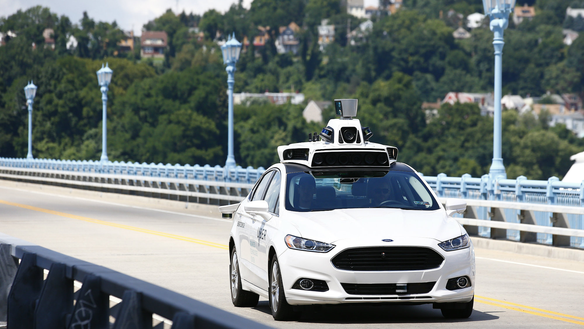 In this Thursday, Aug. 18, 2016, file photo, Uber employees test a self-driving Ford Fusion hybrid car, in Pittsburgh.