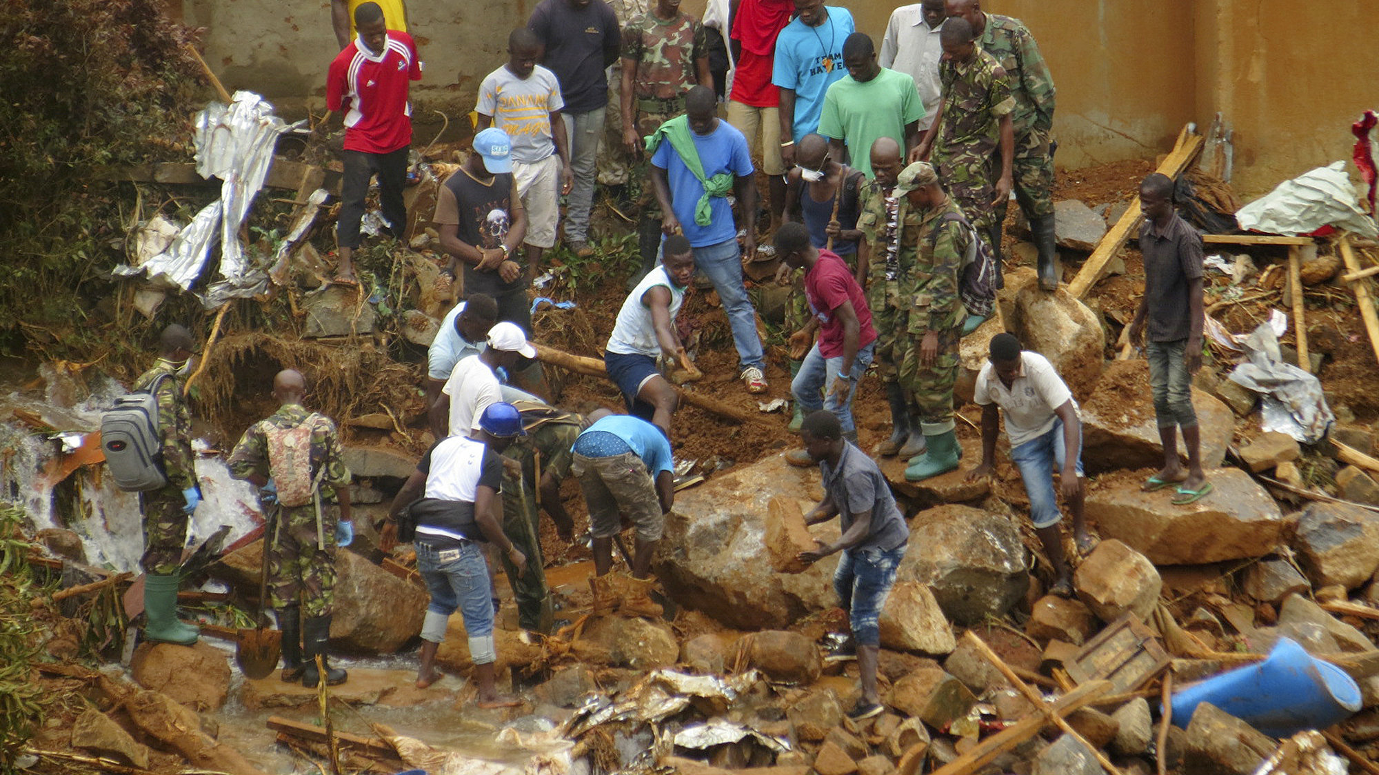 """Volunteers search for bodies from the scene of heavy flooding and mudslides in Regent, just outside of Sierra Leone's capital Freetown. Tuesday, Aug. 15 , 2017. Survivors of deadly mudslides in Sierra Leone's capital are vividly describing the disaster as President Ernest Bai Koroma says the nation is in a """"state of grief."""""""