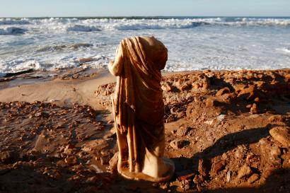 A Roman statue stands on the shore of the Mediterranean sea.