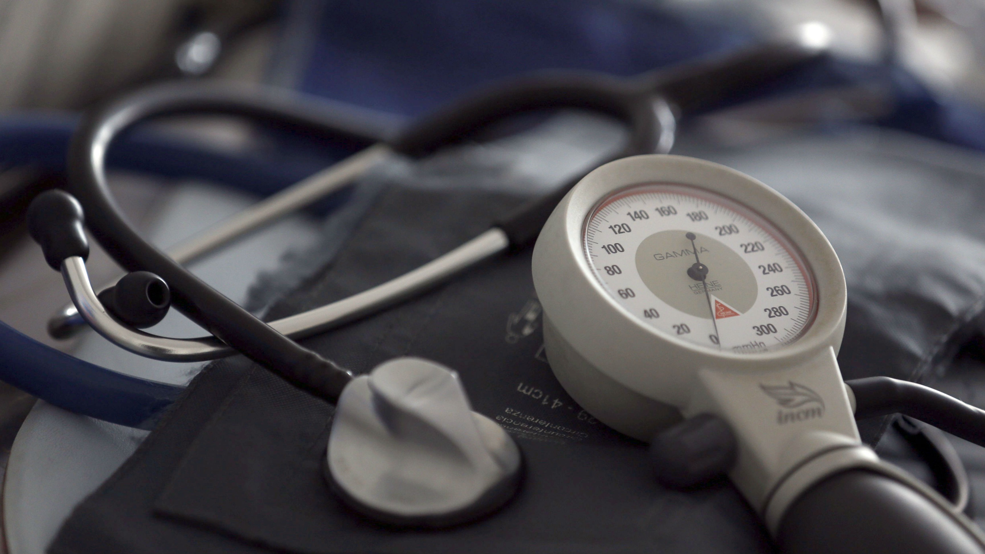 a stethoscope on a table against a blue blood pressure cuff.