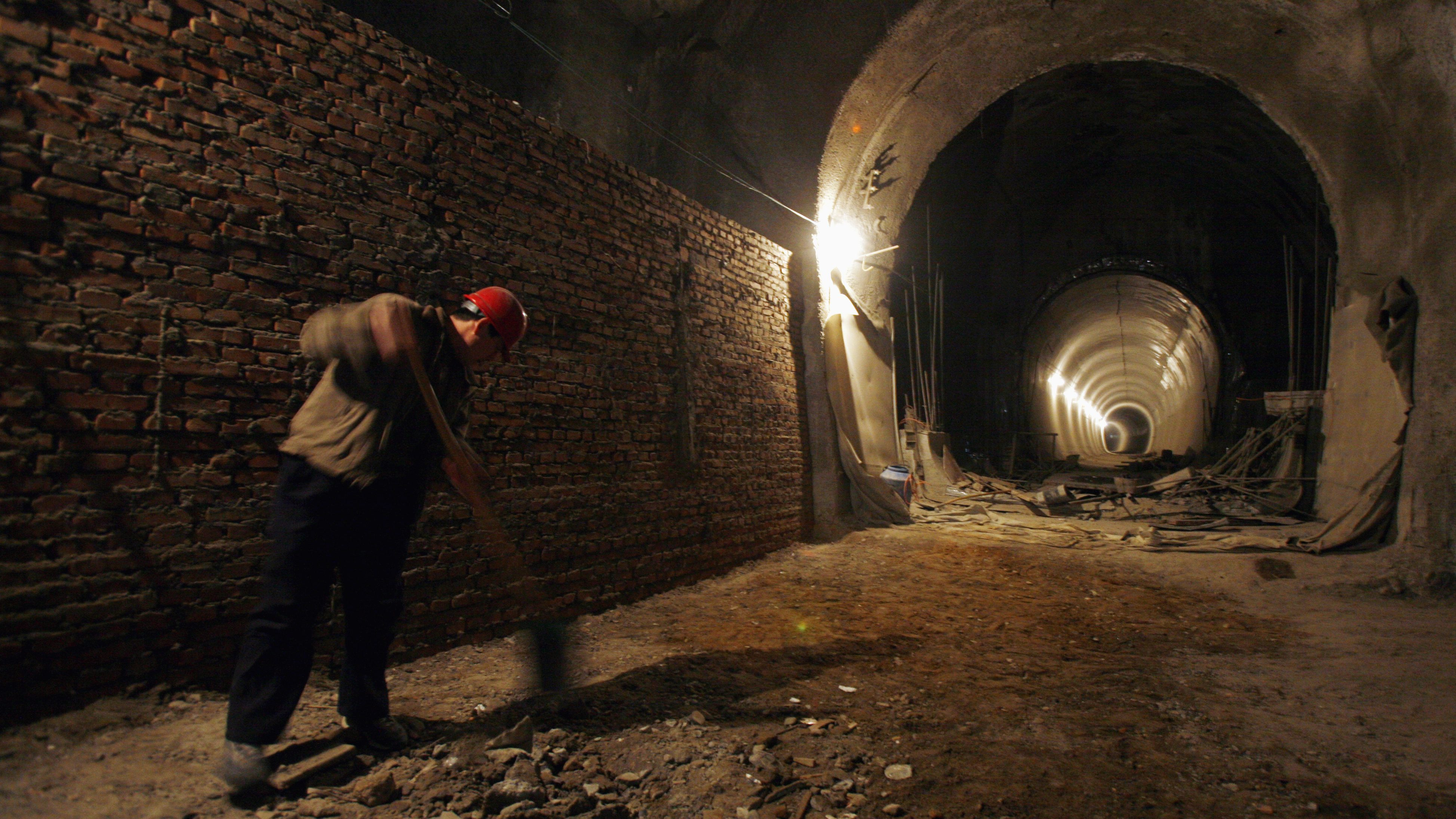 A migrant worker uses a shovel to remove dirt from the floor of one of the railway tunnels under construction in central Beijing January 10, 2008.