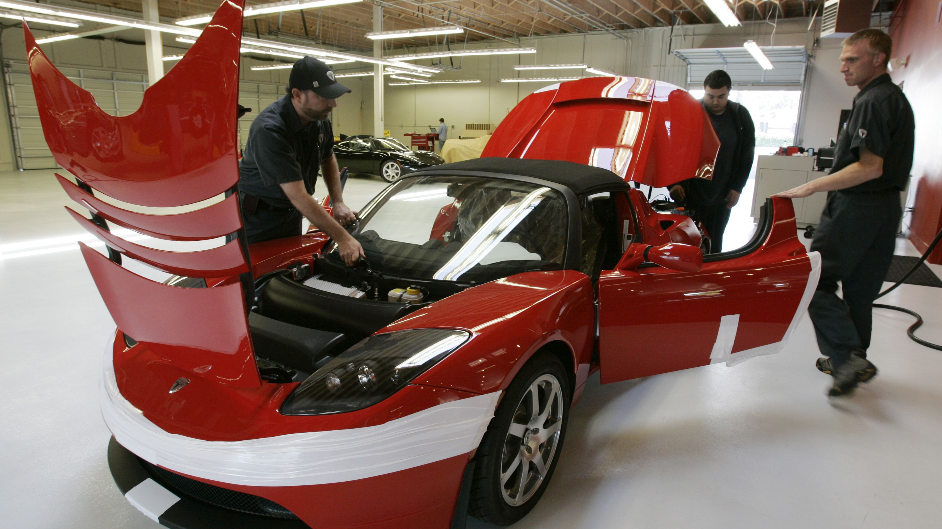 Tesla workers assembly a Tesla Roadster at their showroom in Menlo Park, Calif., Tuesday, Sept. 16, 2008. Tesla expects final approval of a deal with the city of San Jose, Calif., for a plant to build the Model S, an all-electric sedan. Tesla's cars run on a massive lithium-ion battery pack that can be recharged by plugging an adapter cord into a wall socket. (AP Photo/Paul Sakuma)