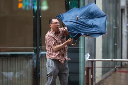 A man struggles with his umbrella as typhoon Hato passes through Hong Kong, China, 23 August 2017. Typhoon signal No 10, the highest in Hong Kong's storm warning system, was issued on 23 August. EPA/JEROME FAVRE