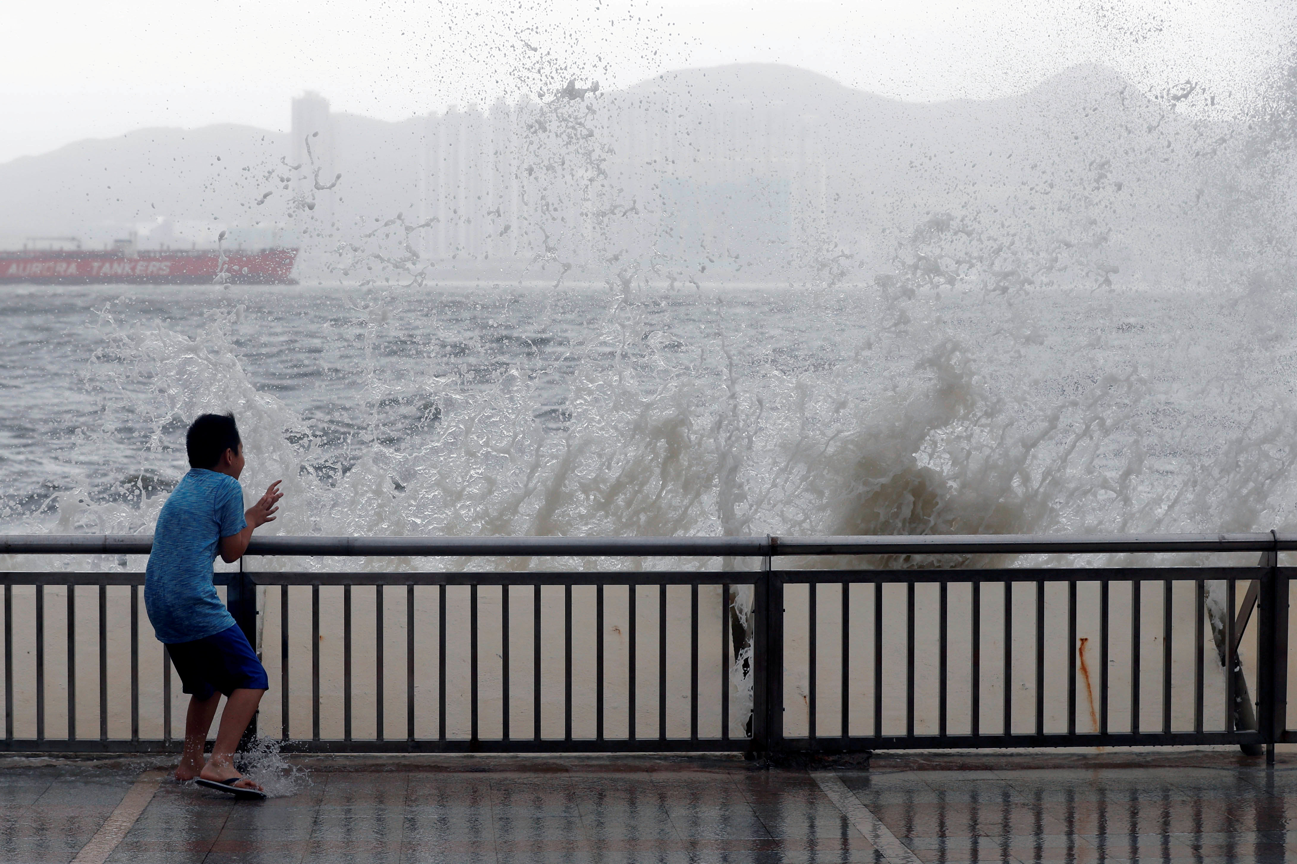 A child reacts after a big wave on a waterfront as Typhoon Hato hits Hong Kong, China August 23, 2017. REUTERS/Tyrone Siu TPX IMAGES OF THE DAY - RTS1CWRT