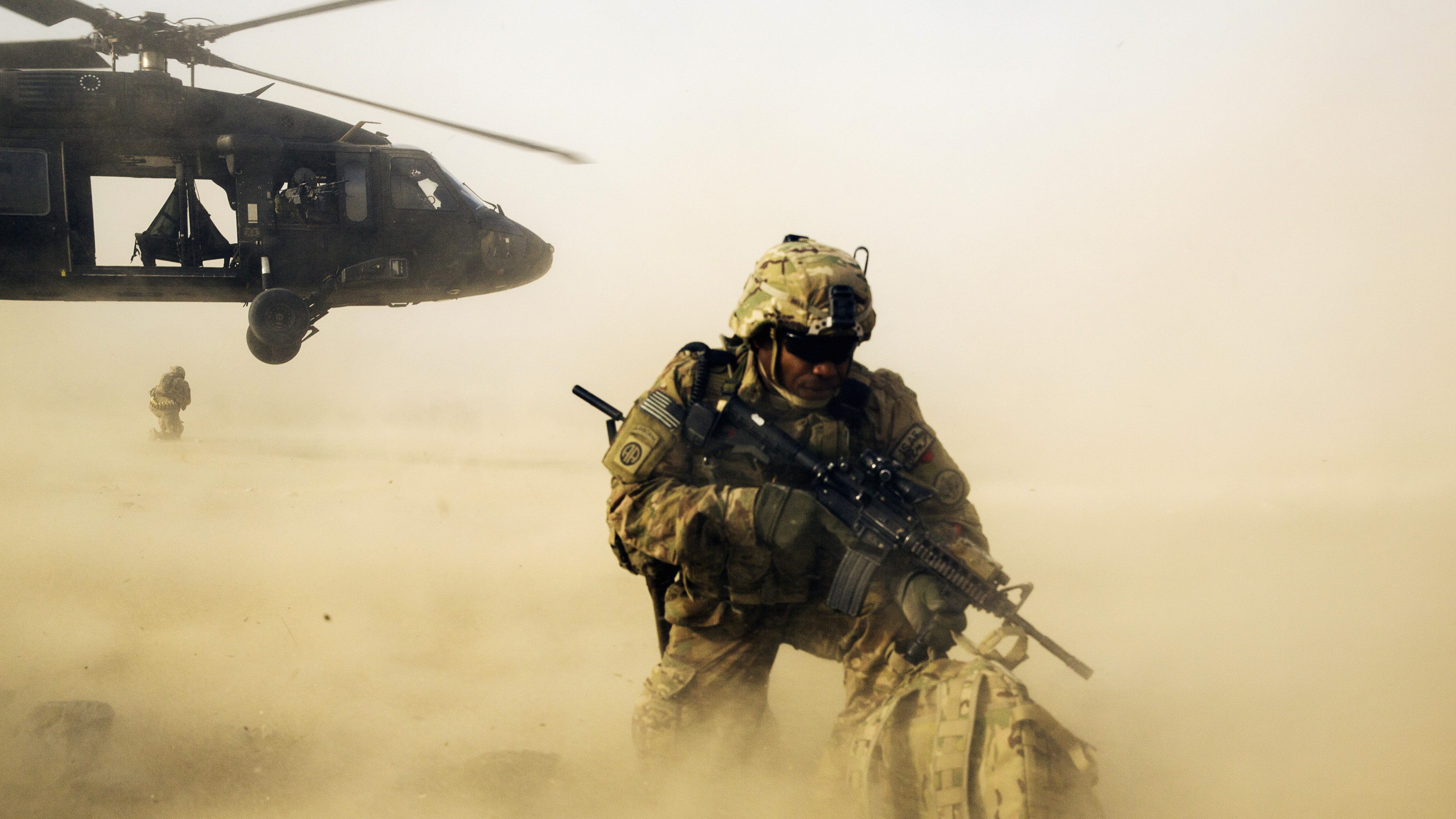 A U.S. soldier from the 3rd Cavalry Regiment shields himself from the rotor wash of a UH-60 Blackhawk helicopter after being dropped off for a mission with the Afghan police near Jalalabad in the Nangarhar province of Afghanistan December 20, 2014. REUTERS/Lucas Jackson (AFGHANISTAN - Tags: TRANSPORT CIVIL UNREST MILITARY POLITICS TPX IMAGES OF THE DAY) - RTR4IRXO