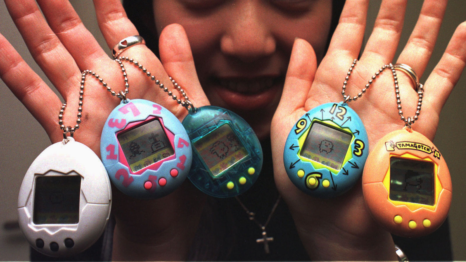 hands holding tamagotchis