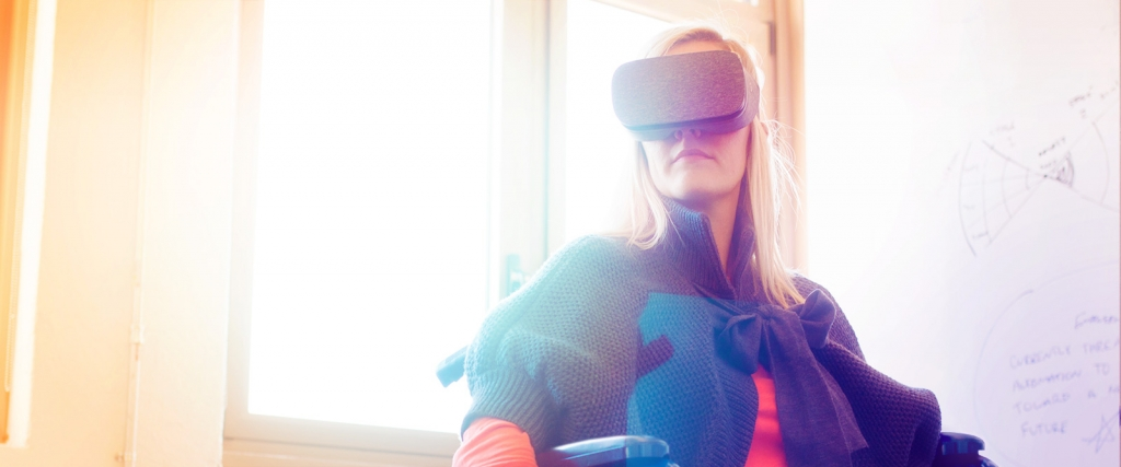 Woman sitting in a wheelchair wears VR headset.