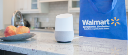 Google Home sits on a countertop in front of a Walmart bag.