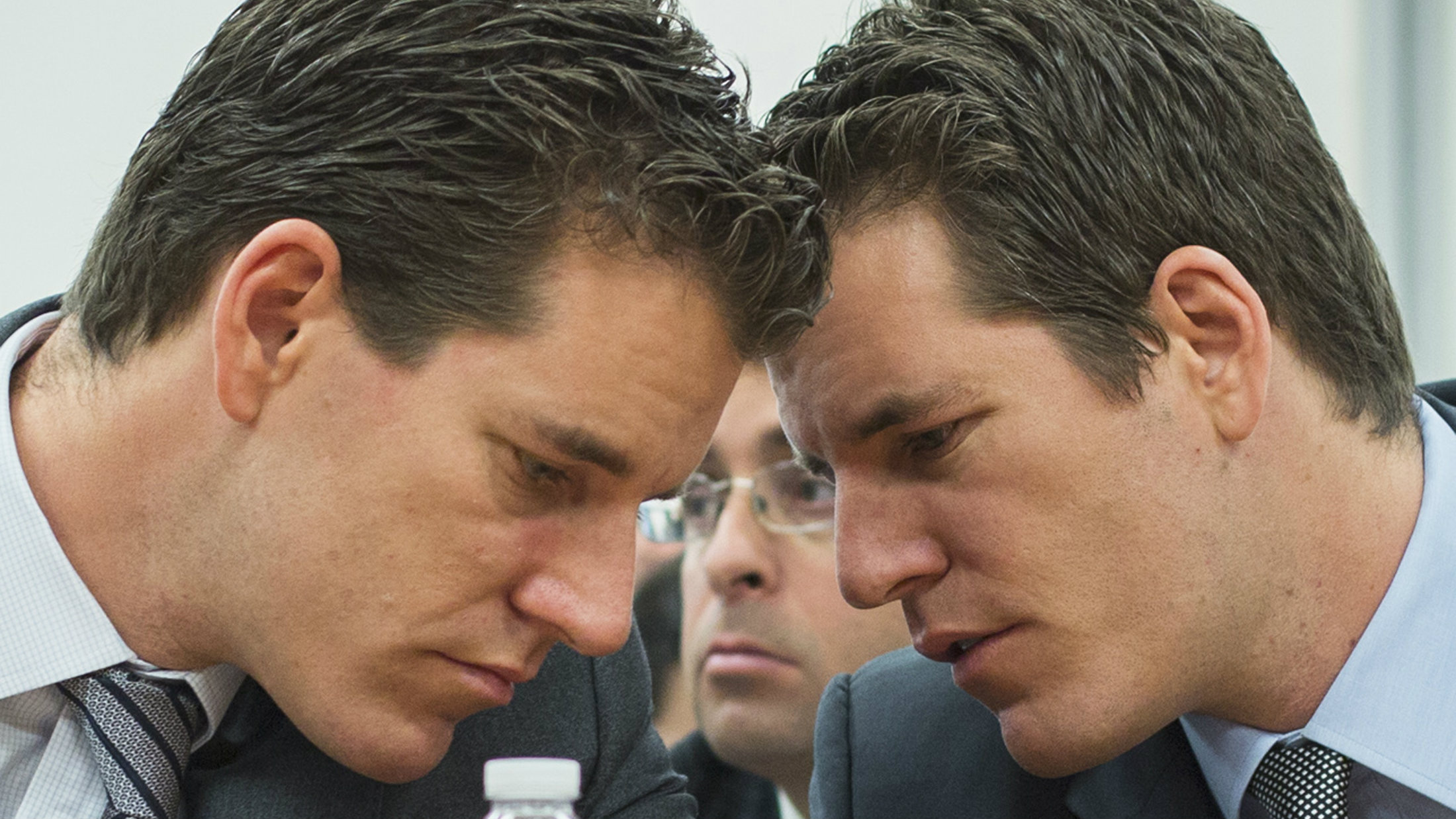 "Brothers Cameron (L) and Tyler Winklevoss talk to each other as they attend a New York State Department of Financial Services (DFS) virtual currency hearing in the Manhattan borough of New York January 28, 2014. New York will propose regulating virtual currency firms that operate in the state this year and may require them to obtain a ""BitLicense,"" state banking regulator Benjamin Lawsky said on Tuesday."