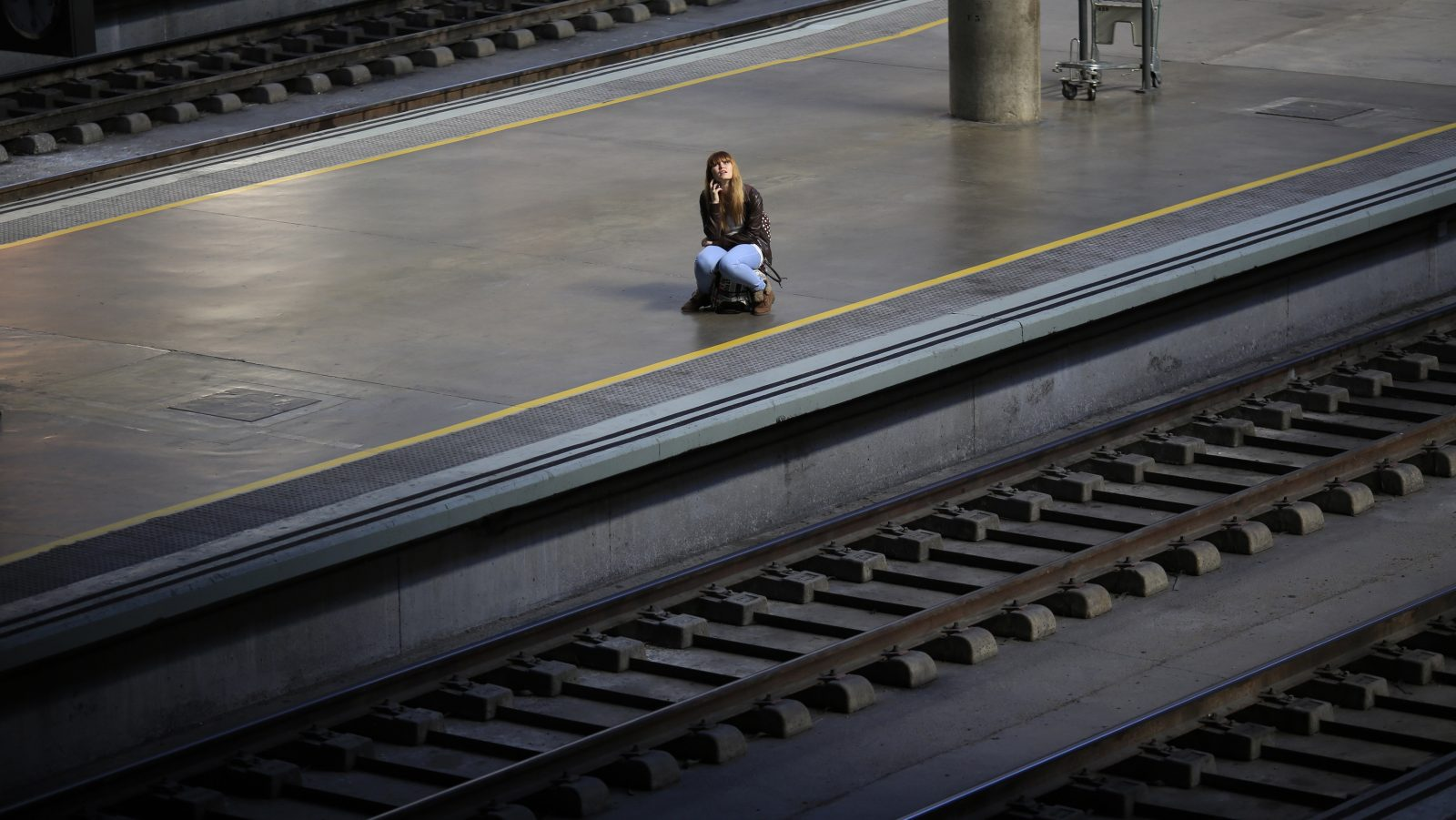 A woman sits on her suitcase as she waits for a train during a 24-hour nationwide train strike against the privatization plans of railways public companies Adif and Renfe at Santa Just train station in the Andalusian capital of Seville, southern Spain October 31, 2013. REUTERS/Marcelo del Pozo (SPAIN - Tags: BUSINESS CIVIL UNREST EMPLOYMENT TRANSPORT TPX IMAGES OF THE DAY) - RTX14UY7
