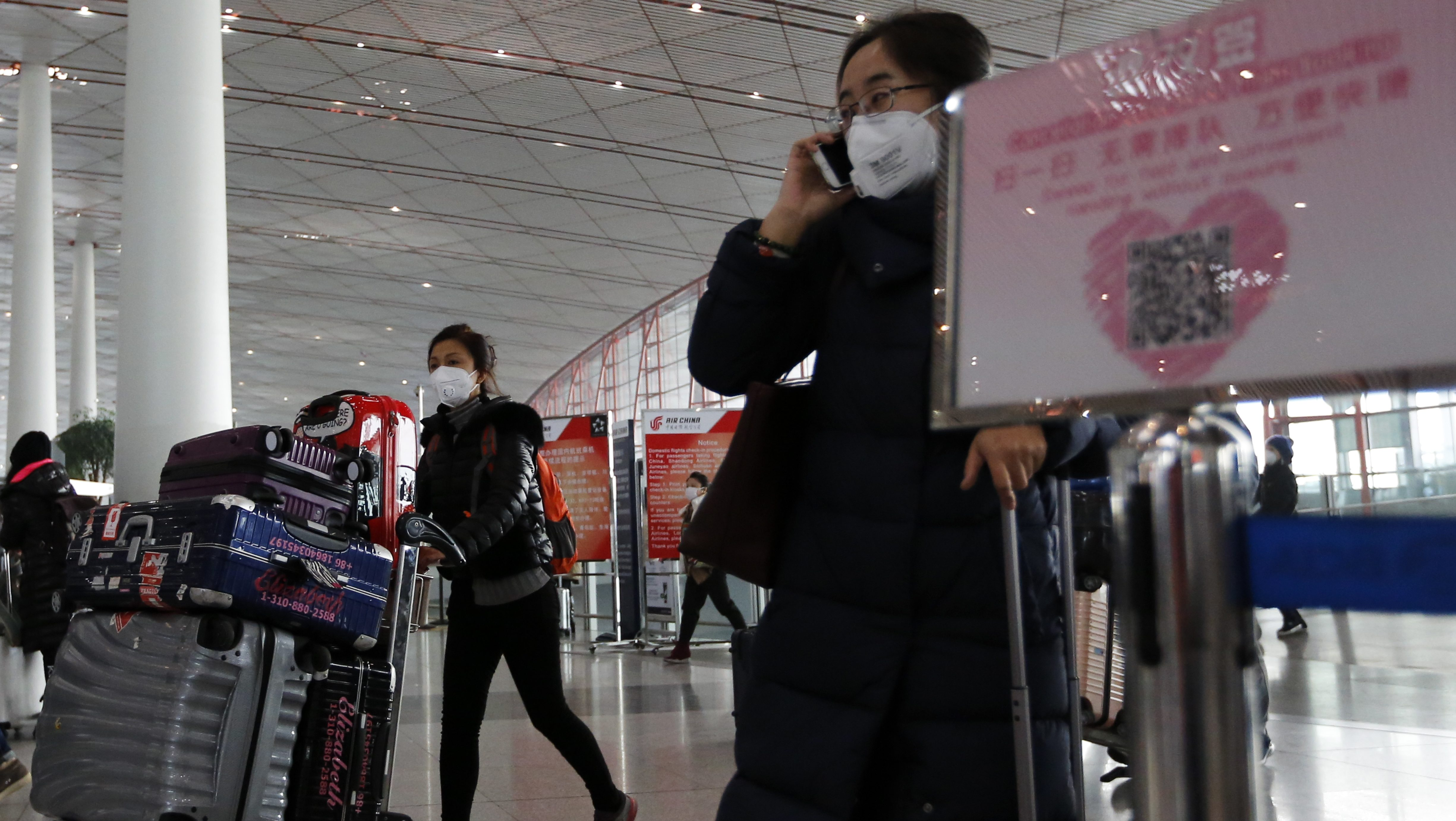 "People wearing masks for protection against air pollution push their luggage at the Beijing Capital International Airport as the capital of China is shrouded by heavy smog on Wednesday, Dec. 21, 2016. Beijing and much of industrial northern China are in the midst of a ""red alert,"" the highest level in China's four-tiered pollution warning system. The alert has affected 460 million people, according to Greenpeace East Asia, which calculated that about 200 million people were living in areas that had experienced levels of air pollution more than 10 times above the guideline set by the World Health Organization. (AP Photo/Andy Wong)"
