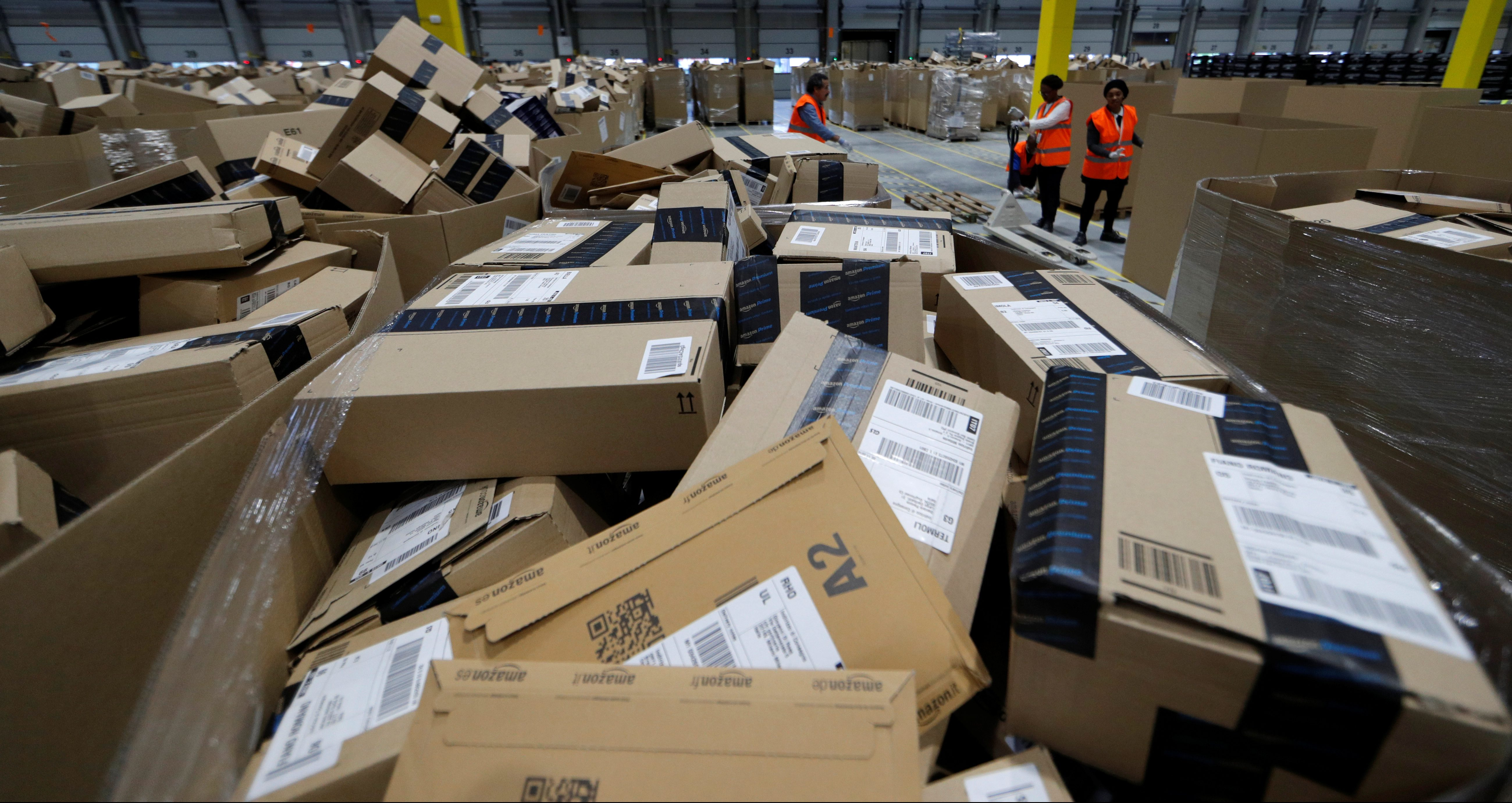 Employees sort packages at the Amazon distribution center warehouse in Saran, near Orleans, France, November 22, 2016.   REUTERS/Philippe Wojazer - RC1C5DD0FF40