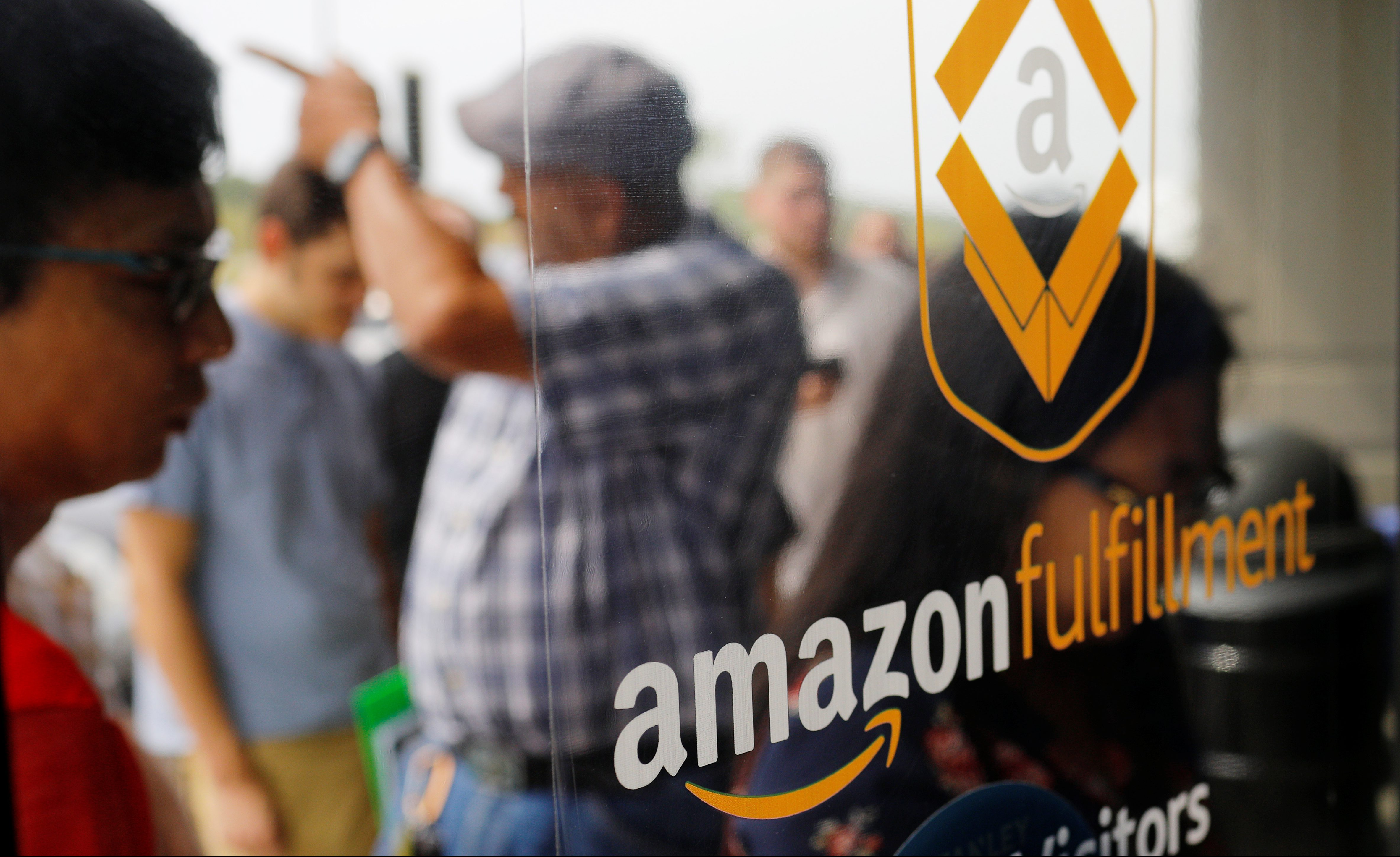 """Job seekers line up to apply during """"Amazon Jobs Day,"""" a job fair being held at 10 fulfillment centers across the United States aimed at filling more than 50,000 jobs, at the Amazon.com Fulfillment Center in Fall River, Massachusetts, U.S., August 2, 2017.   REUTERS/Brian Snyder - RC1AB22F98F0"""