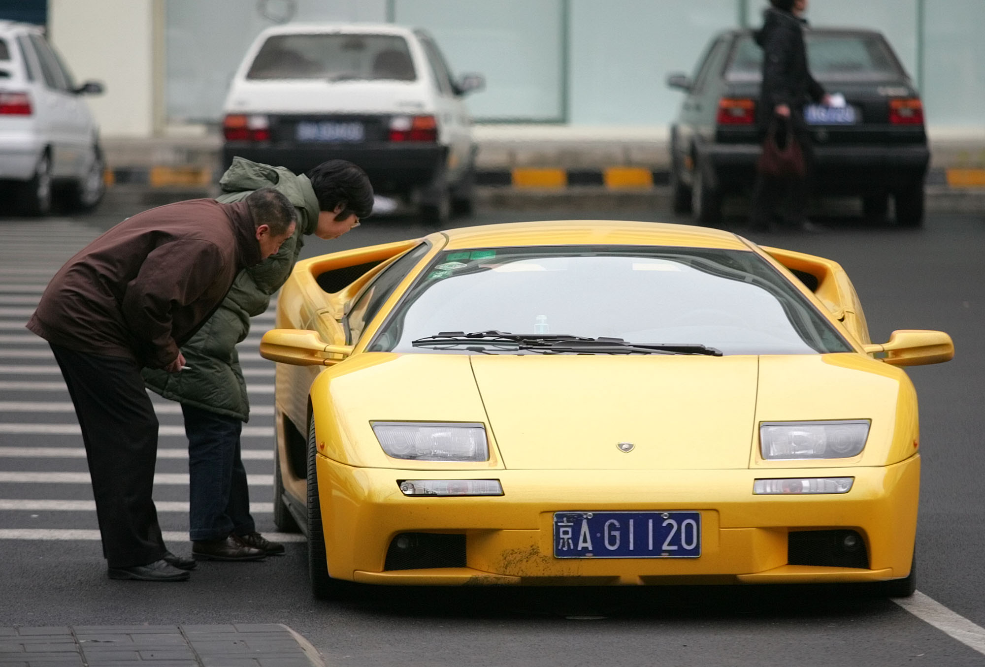 A couple get a close-up look at a Lamborghini Diablo VT parked in Beijing Thursday, Dec. 16, 2004. Two decades of economic reforms in China have resulted in riches for some, but at least 29 million people still live below poverty levels, according to government figures.