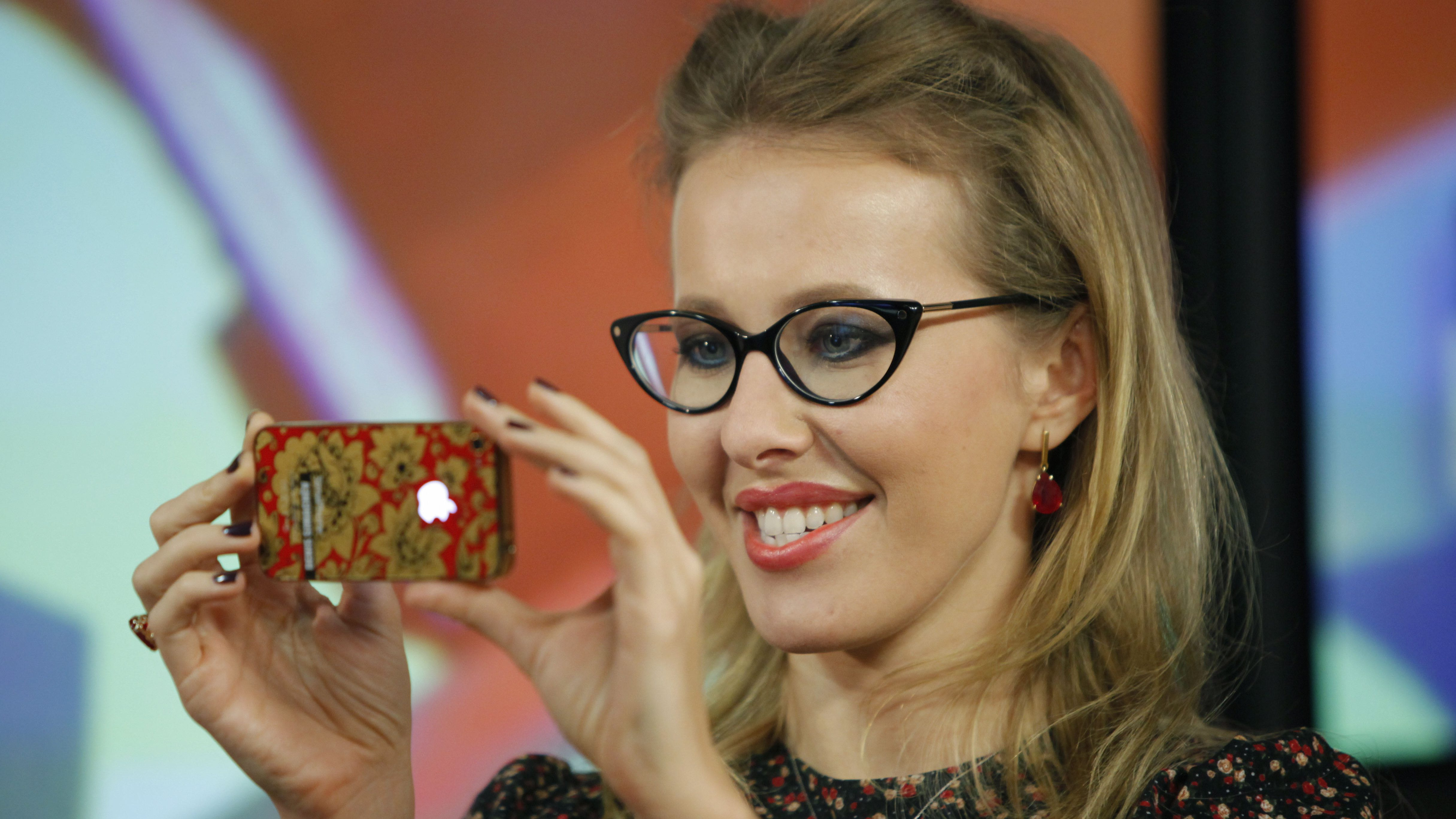 "FILE - In this Wednesday, Jan. 18, 2012 file photo Russian socialite and TV host Kseniya Sobchak, daughter of the late St. Petersburg mayor, Anatoly Sobchak, takes a photo of journalists during her interview in the Echo Moskvy (Echo of Moscow) radio station in Moscow, Russia. ""I'm Ksenia Sobchak, and I've got something to lose. But I'm here."" This is what the 30-year-old blond socialite and TV personality said when she began her unlikely foray into political activism by taking the stage at a huge anti-Putin rally in December. Once considered untouchable because of her family's close personal ties to President Vladimir Putin, Sobchak has since found that she does indeed have something to lose, as her apartment has been raided by police and she has been called in for interrogation. It has been a quick change of fortune for Russia's It Girl, who like many Russians of her generation experienced a civic awakening after many years of political passivity. (AP Photo/Alexander Zemlianichenko, file)"