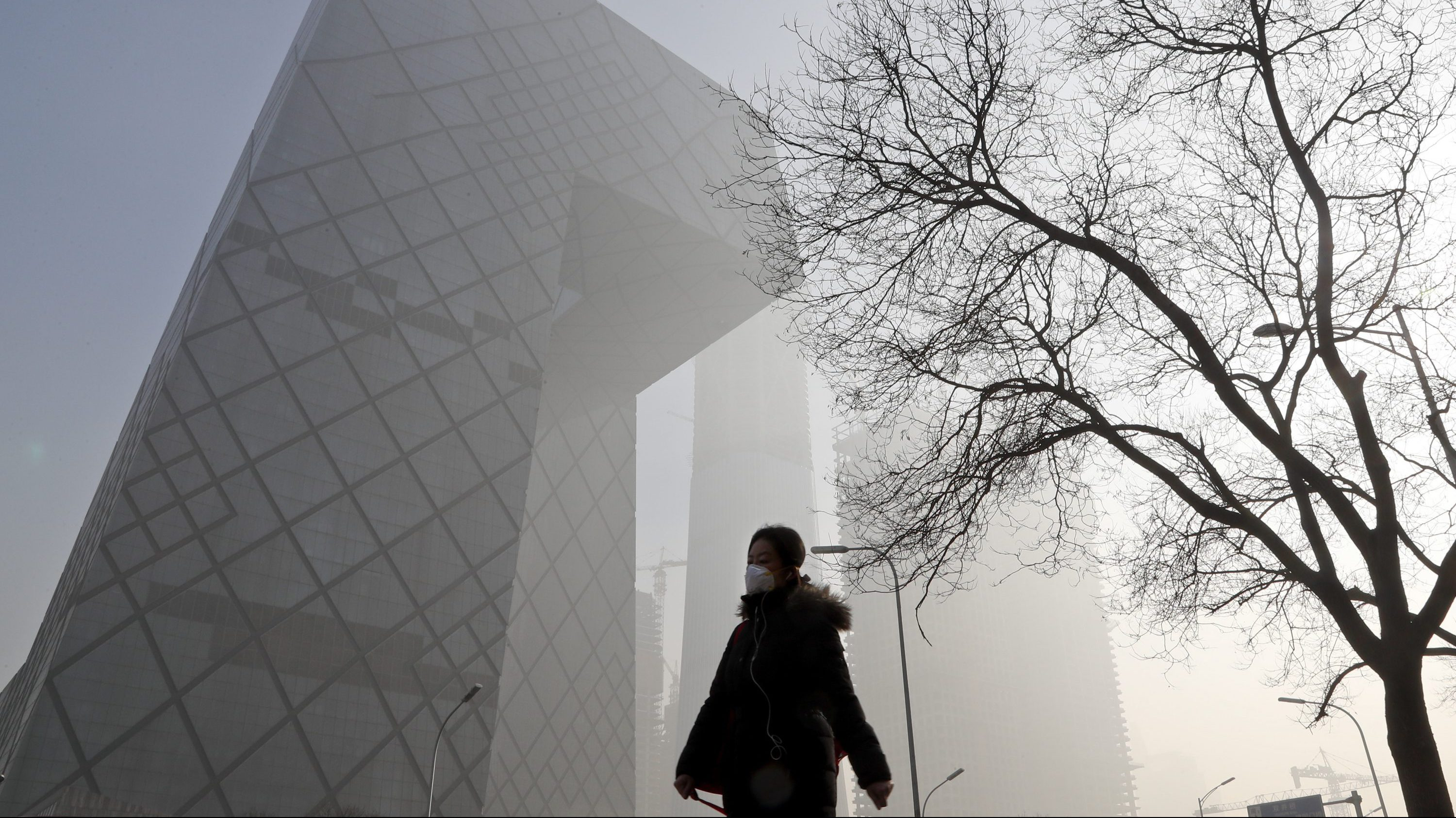 """A Chinese woman wearing a protection mask walks near the iconic headquarters of China's state broadcaster Central China Television (CCTV) at the Central Business District in Beijing as the capital of China is blanked by heavy smog Tuesday, Jan. 3, 2017. China's Ministry of Environment says an unspecified number of companies have violated measures meant to reduce smog as the country deals with a phase of particularly noxious pollution. Beijing has been on """"orange alert"""" the second highest pollution alert level since Friday. The alert was originally due to end on Sunday but authorities have extended it a further three days."""