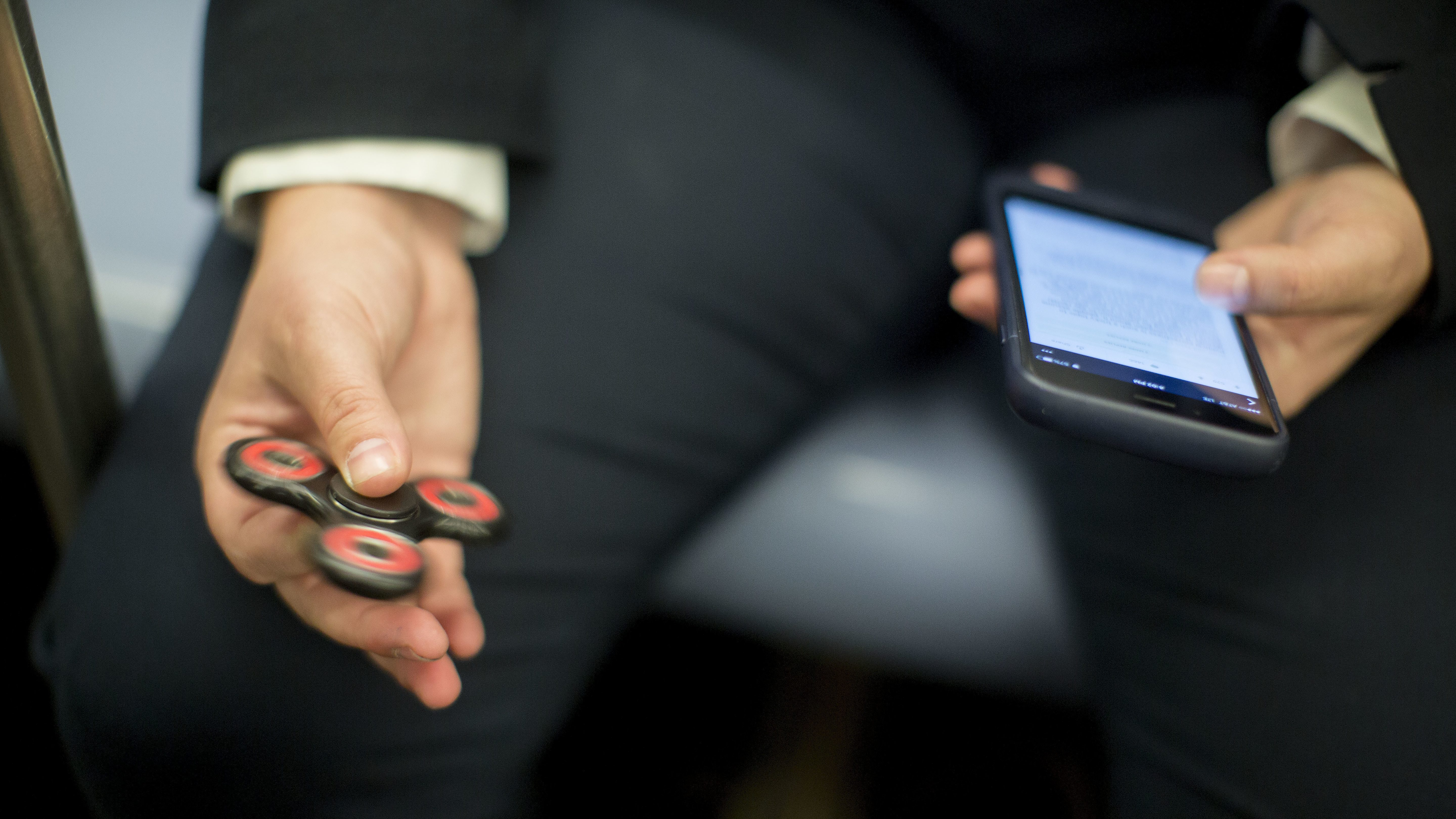 In this Wednesday, May 10, 2017, photo, attorney Kim Juszczak uses a fidget spinner while riding the subway in New York. Fidget spinners have been around for years, mostly used by kids with autism or attention disorders to help them concentrate. But they exploded in popularity this spring. Juszczak likes to whirl her spinner on the subway or while she's thinking up legal arguments for a case. (AP Photo/Mary Altaffer)