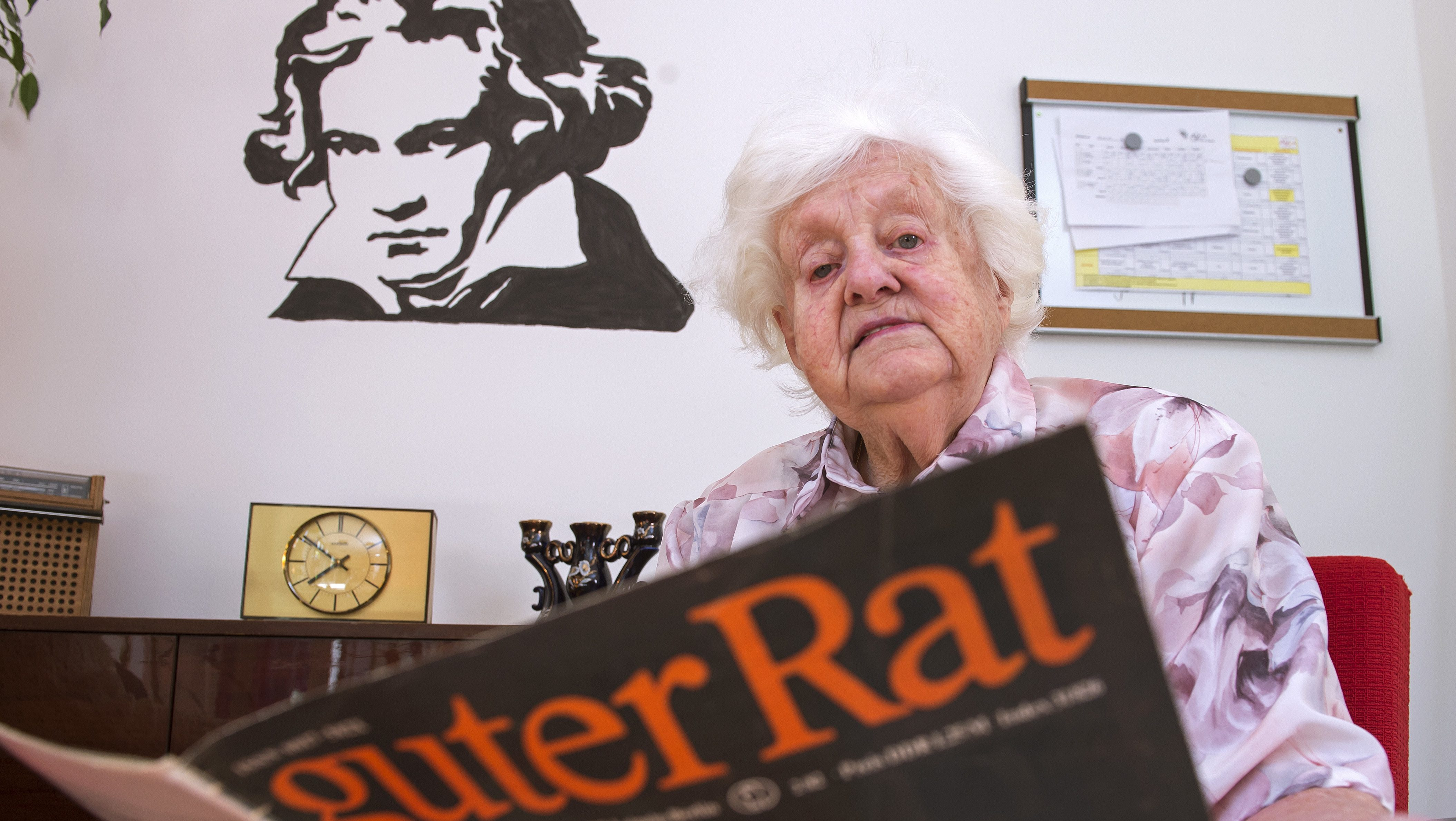 In this May 17, 2017 photo a resident reads in a GDR magazine in the Alexa Seniors' Residence in Dresden, eastern Germany, Wednesday. The words read: 'Good advice'. The retirement home has recreated the communist era of the former GDR in two living-rooms to help residents with Alzheimer's and dementia. (AP Photo/Jens Meyer)