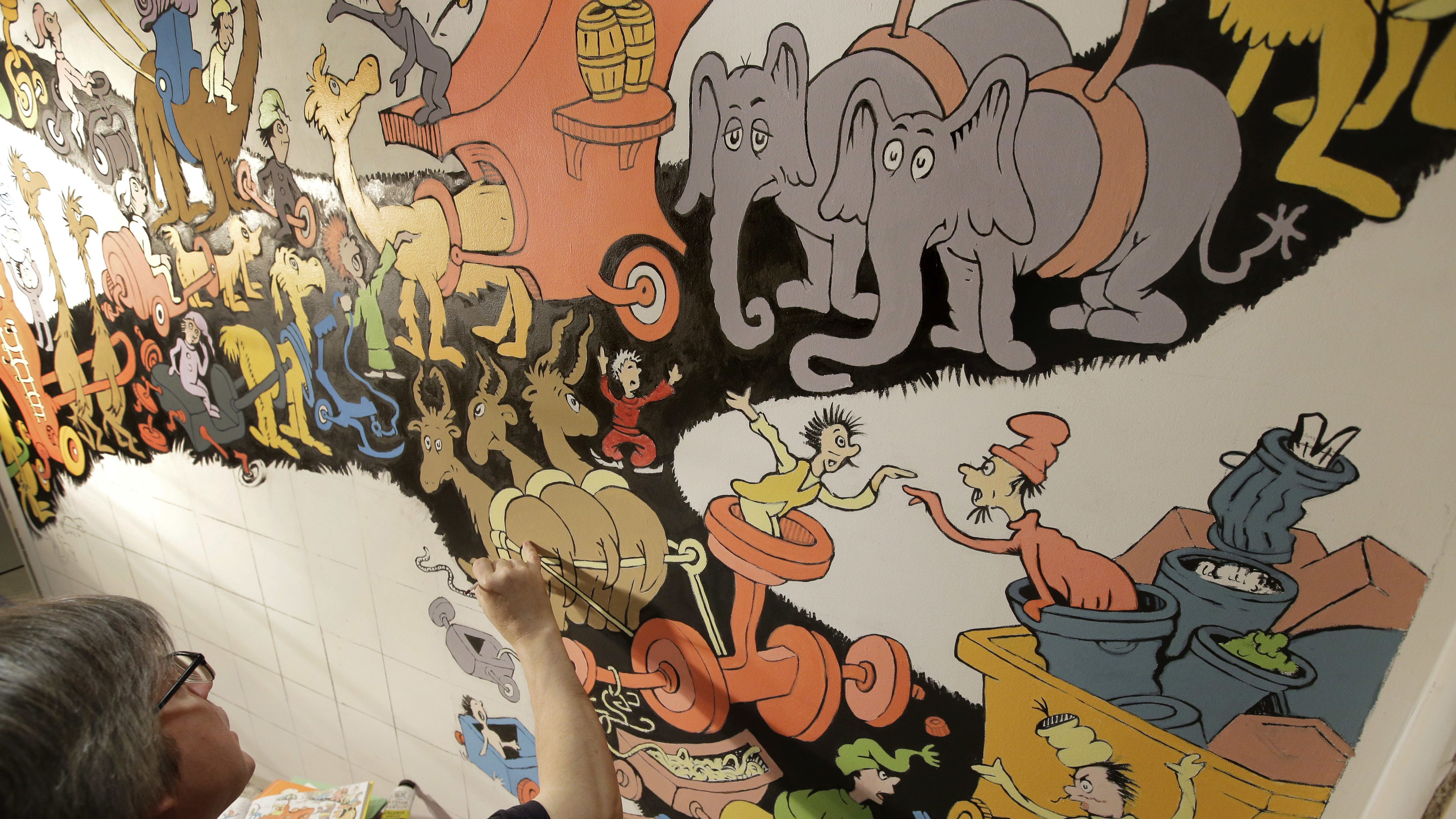 "In this May 4, 2017 photo John Simpson, left, project director of exhibitions for The Amazing World of Dr. Seuss Museum, paints a mural based on artwork in the Dr. Seuss book ""Did I Ever Tell You How Lucky You Are?"" on a wall at the museum, in Springfield, Mass. The new museum devoted to Dr. Seuss, which opened on June 3 in his hometown, features interactive exhibits, a collection of personal belongings and explains how the childhood experiences of the man, whose real name is Theodor Geisel, shaped his work. (AP Photo/Steven Senne)"