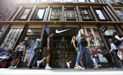 People walk by the Nike SoHo store, Thursday, June 15, 2017, in the SoHo neighborhood of New York. Nike said Thursday that it plans to sell more shoes directly to customers online as part of a restructuring in which it plans to cut about 1,400 jobs. It will also reduce the number of sneaker and clothing styles it makes by a quarter and focus on hot sellers. (AP Photo/Michael Noble Jr.)