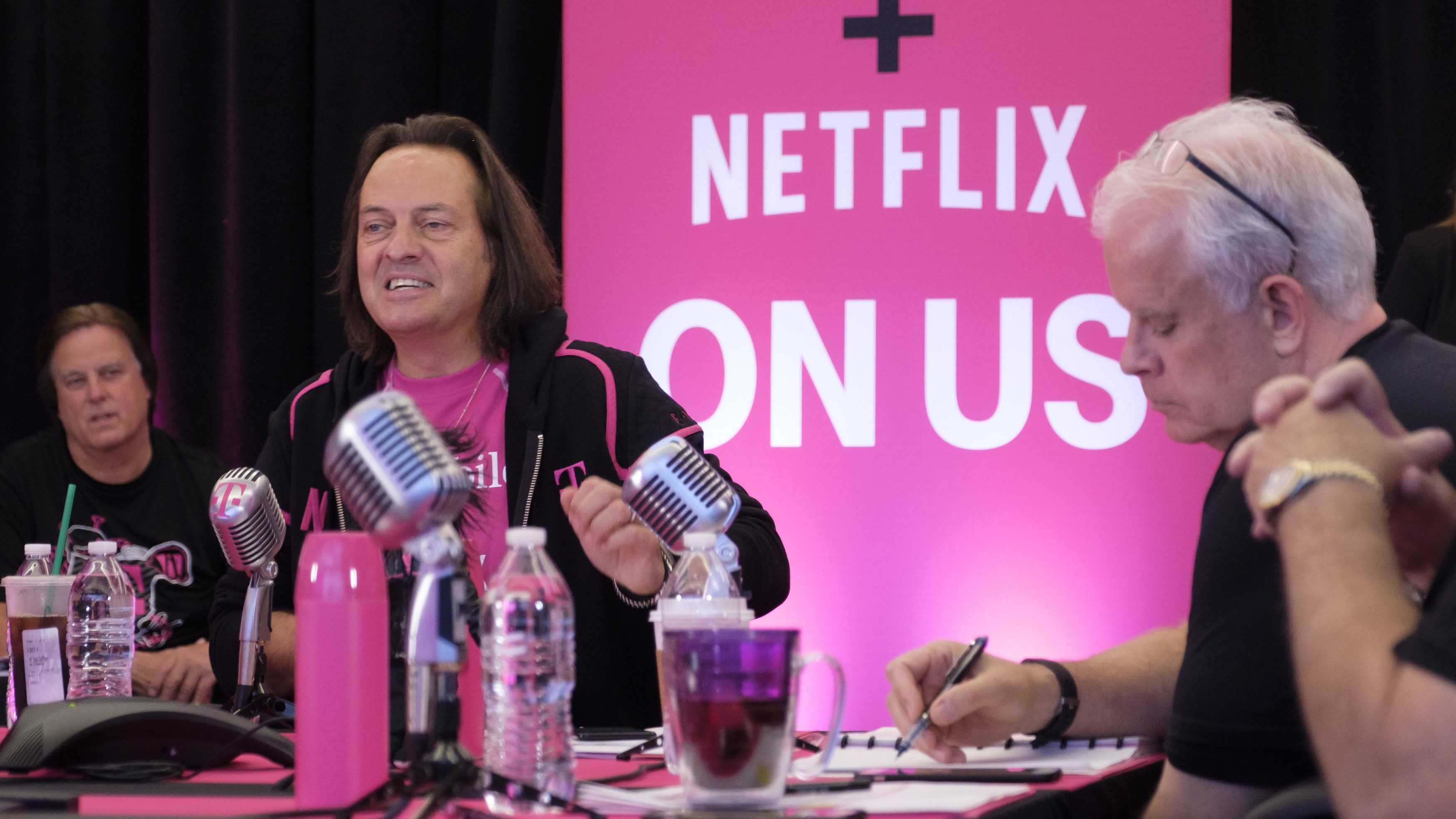 IMAGE DISTRIBUTED FOR T-MOBILE - T-Mobile President and CEO John Legere, second, from left, speaks during the T-Mobile Netflix On Us Un-Carrier event on Wednesday, Sept. 6, 2017 in Bellevue, Wash. T-Mobile announced Netflix now comes free with T-Mobile ONE family plans. At right is T-Mobile Chief Technology Officer Neville Ray. (Stephen Brashear/AP Images for T-Mobile)