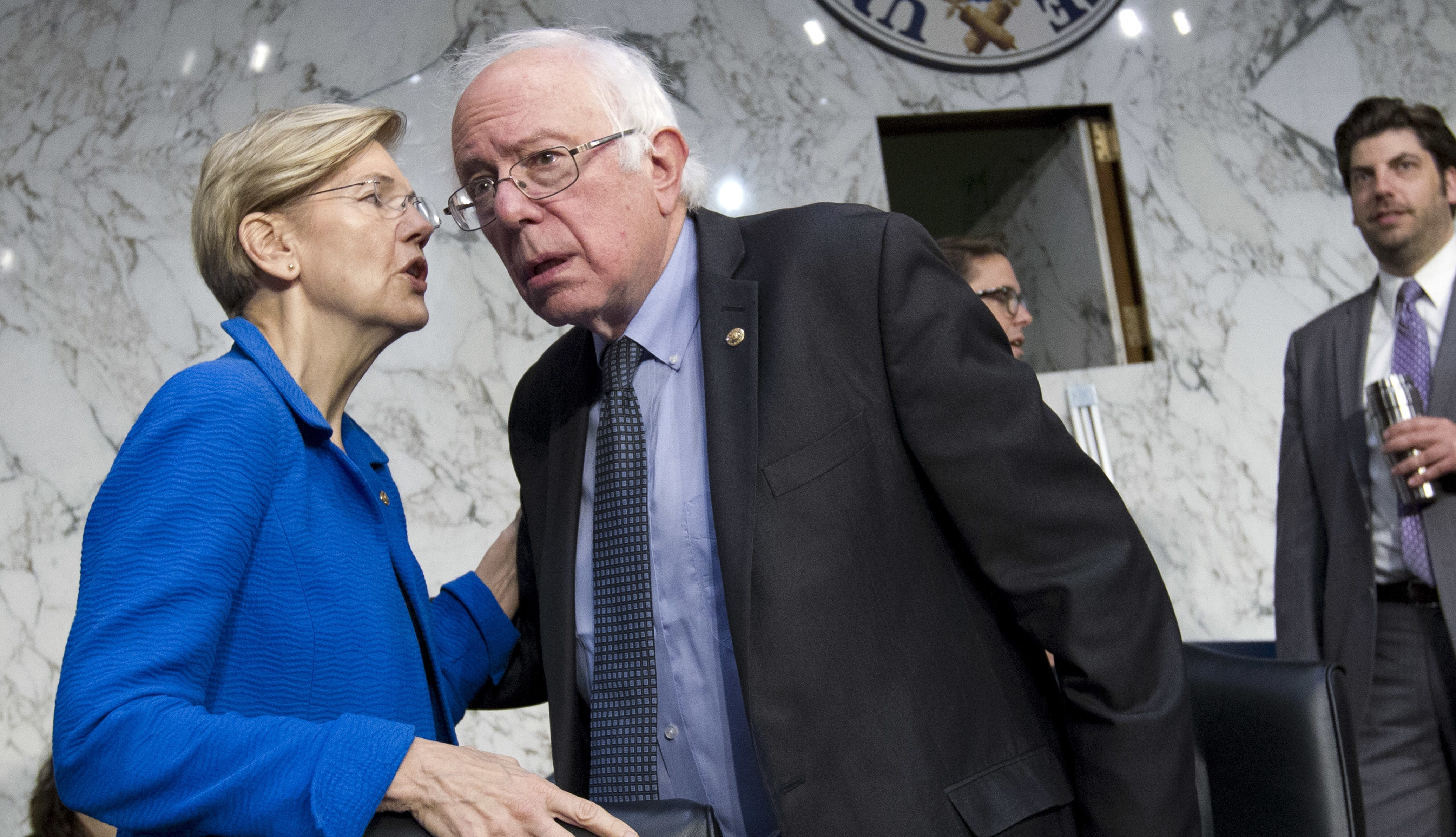 Sen. Elizabeth Warren, D-Mass. speaks with Sen. Bernie Sanders, I-Vt. at the Senate Health, Education, Labor, and Pensions Committee hearing with governors to discuses ways to stabilize health insurance markets, on Capitol Hill in Washington, Thursday, Sept. 7, 2017. ( AP Photo/Jose Luis Magana)