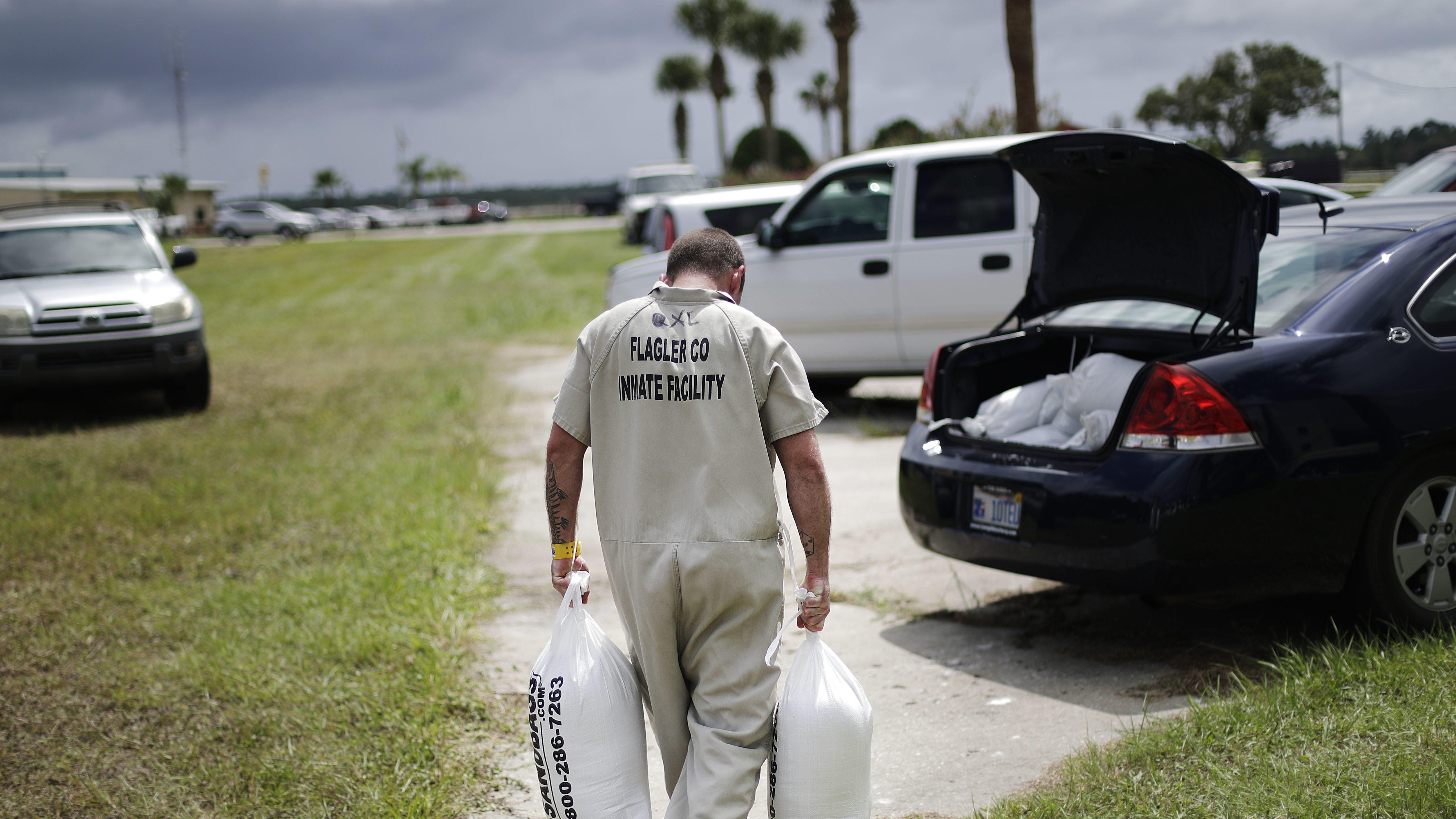 Inmate Eric Sumner carries sandbags for a resident at a makeshift filling station provided by the county as protection ahead of Hurricane Irma in Palm Coast, Fla., Friday, Sept. 8, 2017. (AP Photo/David Goldman)