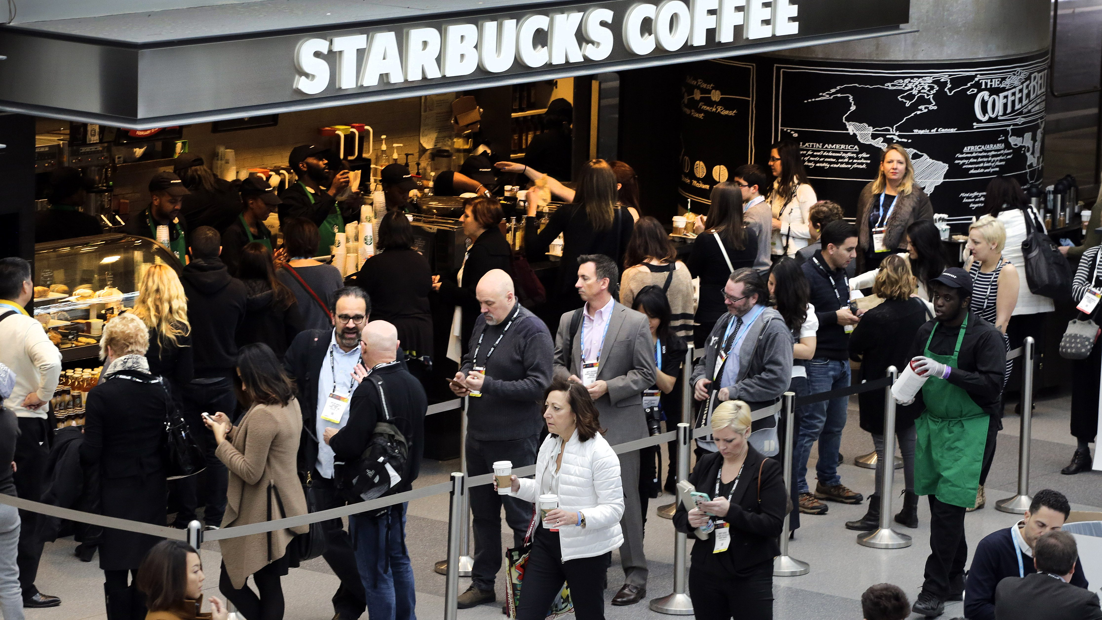 Customers line up at a Starbucks Coffee, Monday, Feb. 15, 2016, in New York.