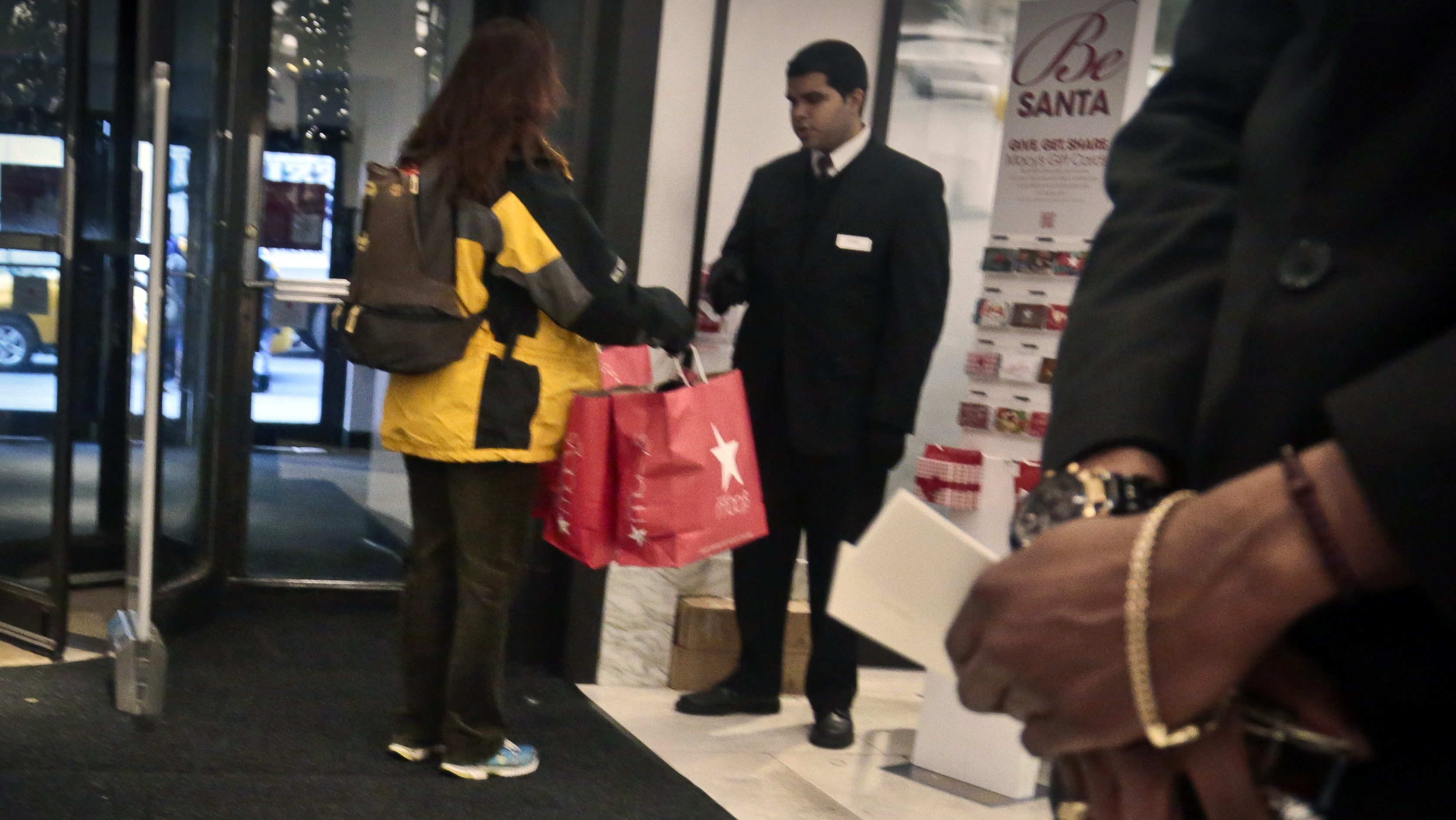In this Dec. 13, 2013 photo, a security agent checks the bags of a shopper at Macy's in New York.  Claims over racial profiling at department stores in New York have helped expose the practice in more than 40 states of retailers holding shoplifting suspects and assessing fines, even if a person hasn't yet technically stolen anything.  At Macy's flagship store, suspects are held in cells, asked to sign an admission of guilt and pay hundreds in fines. (AP Photo/Bebeto Matthews)