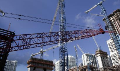 This Thursday, July 24, 2014 photo shows construction cranes at the Brickell City Centre project in downtown Miami. According to real estate license applications in 2013, the number of U.S. real estate agents is increasing as the housing market recovers from the Great Recession.